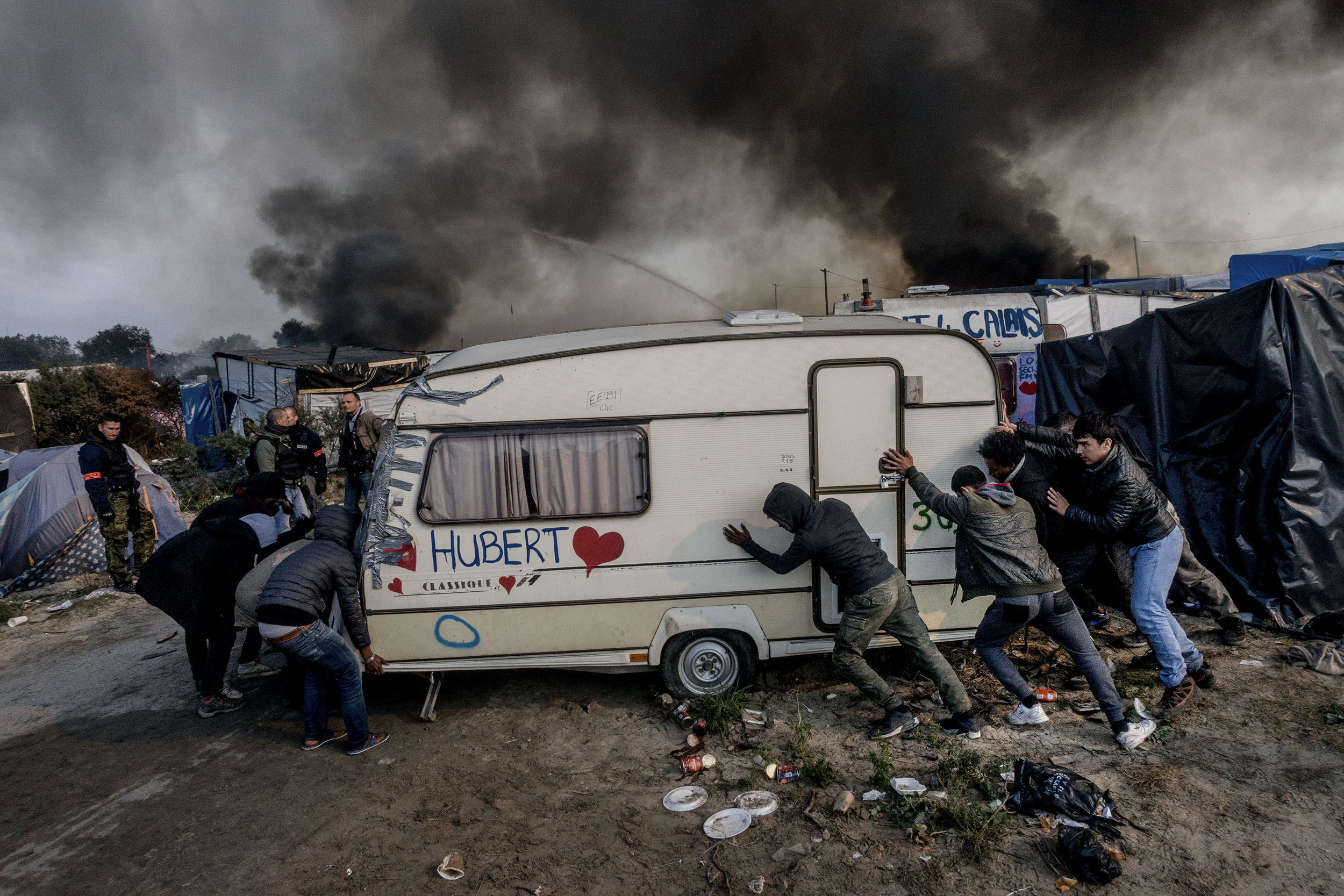 26th October 2016, The Jungle of Calais in France is in huge fire. Few migrants push their caravan to save from fire.