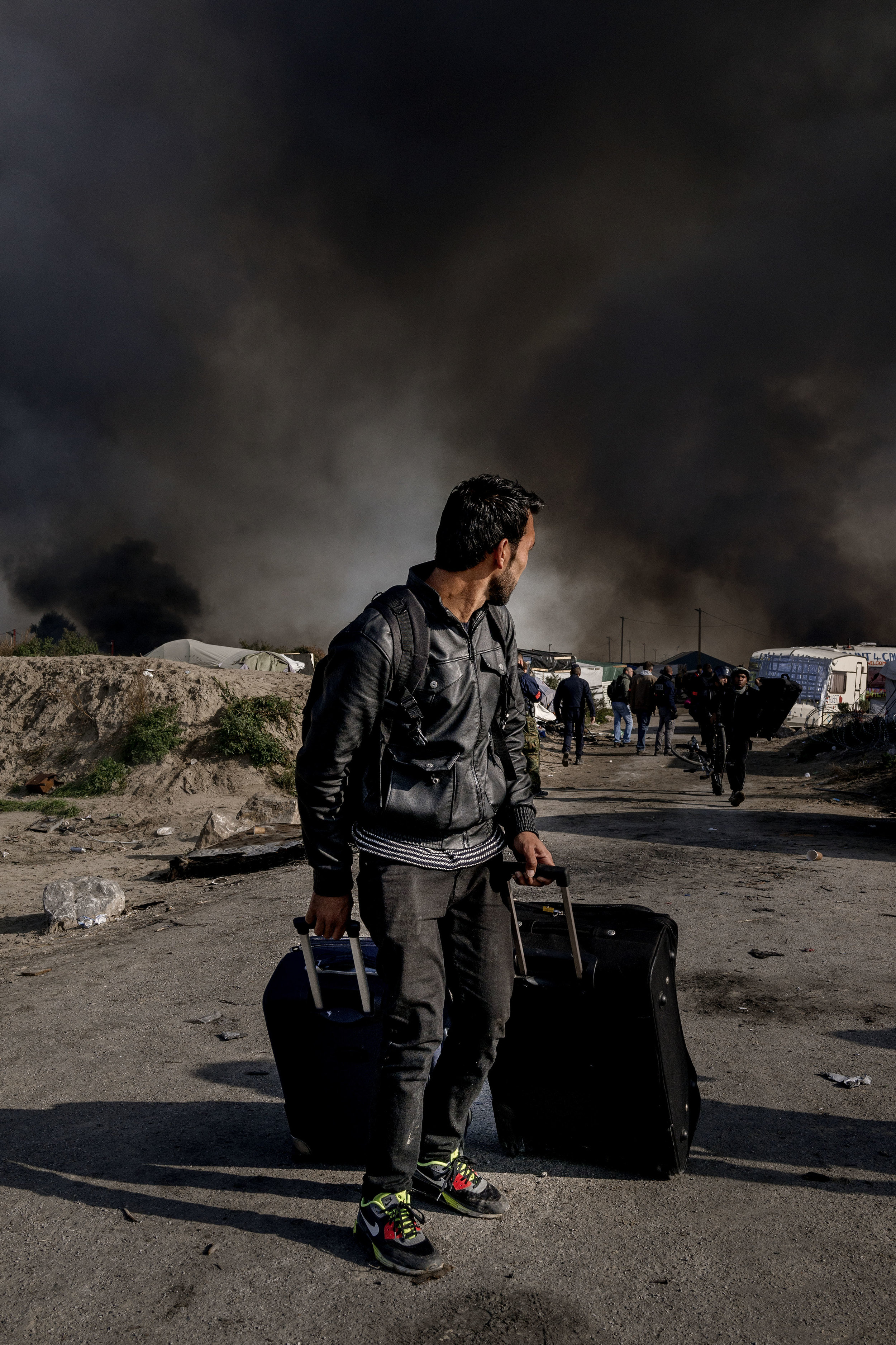 26th October 2016, The Jungle of Calais in France is in huge fire. Refugee leave the camp.