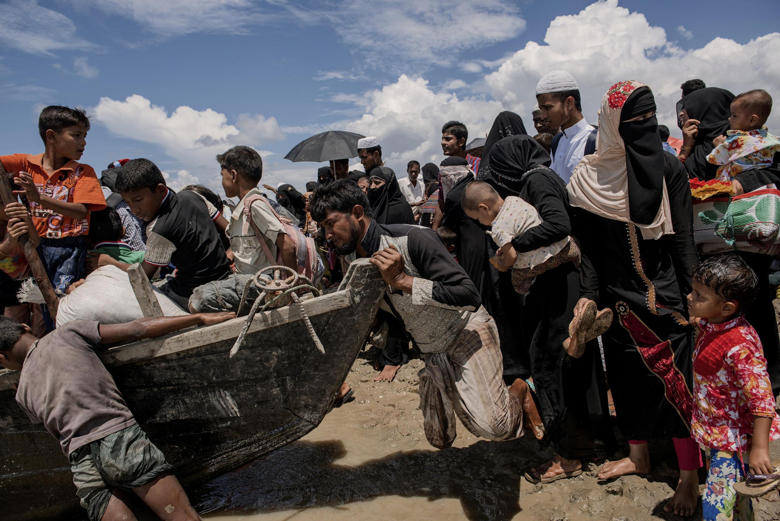TEKNAF, BANGLADESH- SEPTEMBER 13:  Rohingya refugees try get on a boat from Shahporir Island to Teknaf mainland after landing on the Bangladesh shore of Naf river.