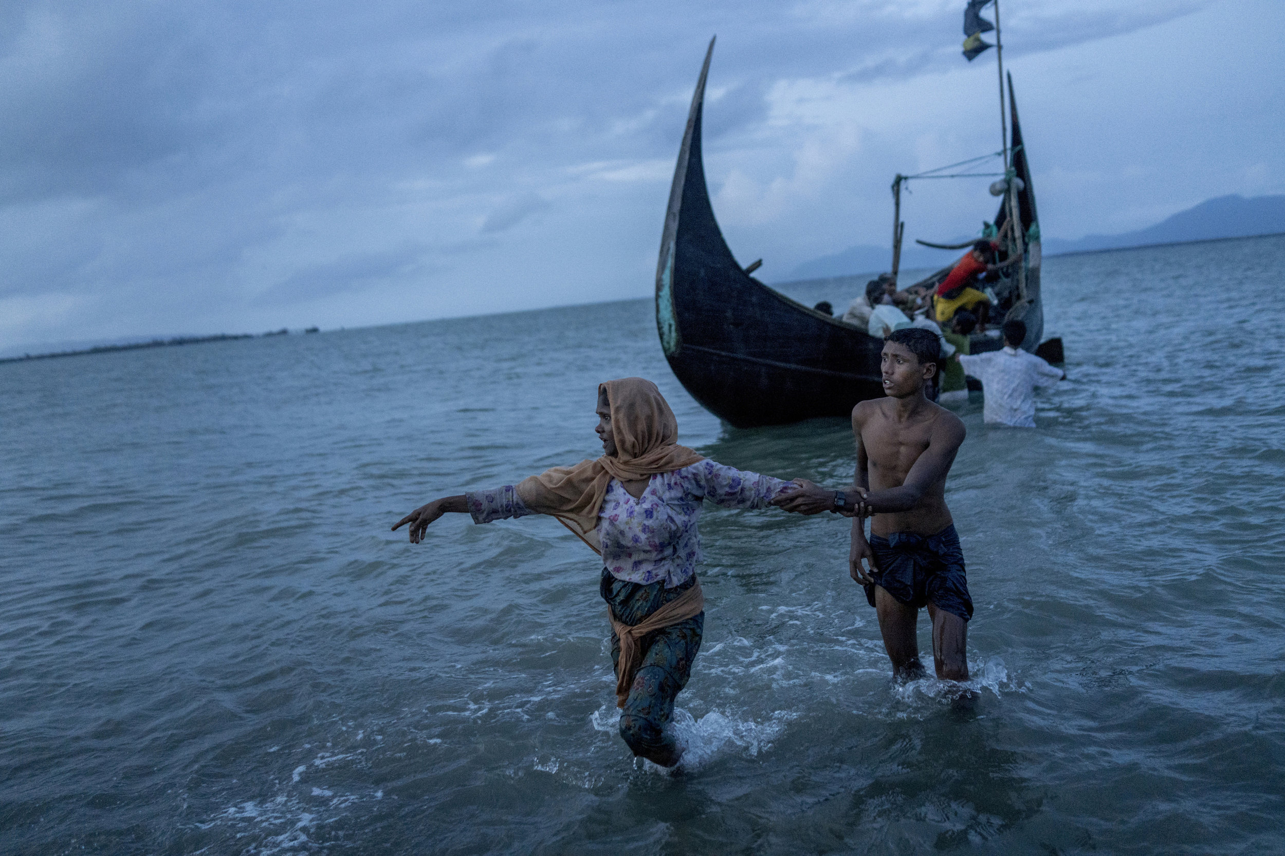 A Rohingya woman lands in the shore of Bangladesh in Teknaf from Myanmar. She looks for her daughter who also crossed the sea border with her.