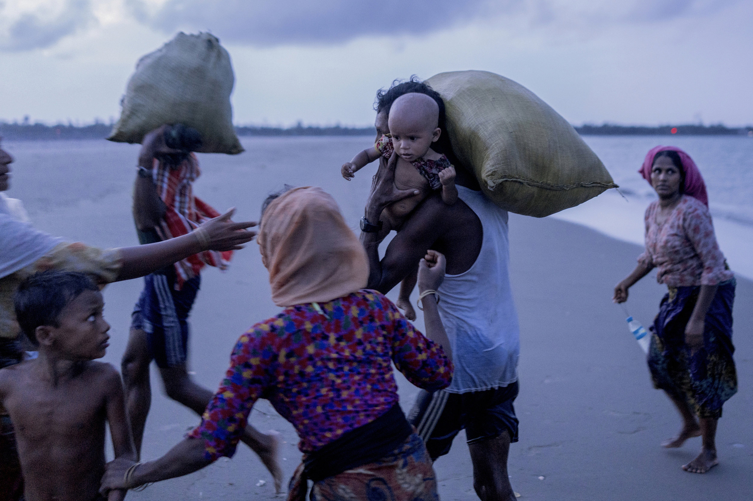 A Rohingya baby girl is carried by a man from drowning when she got off the boat at the Bangladesh border between Myanmar.