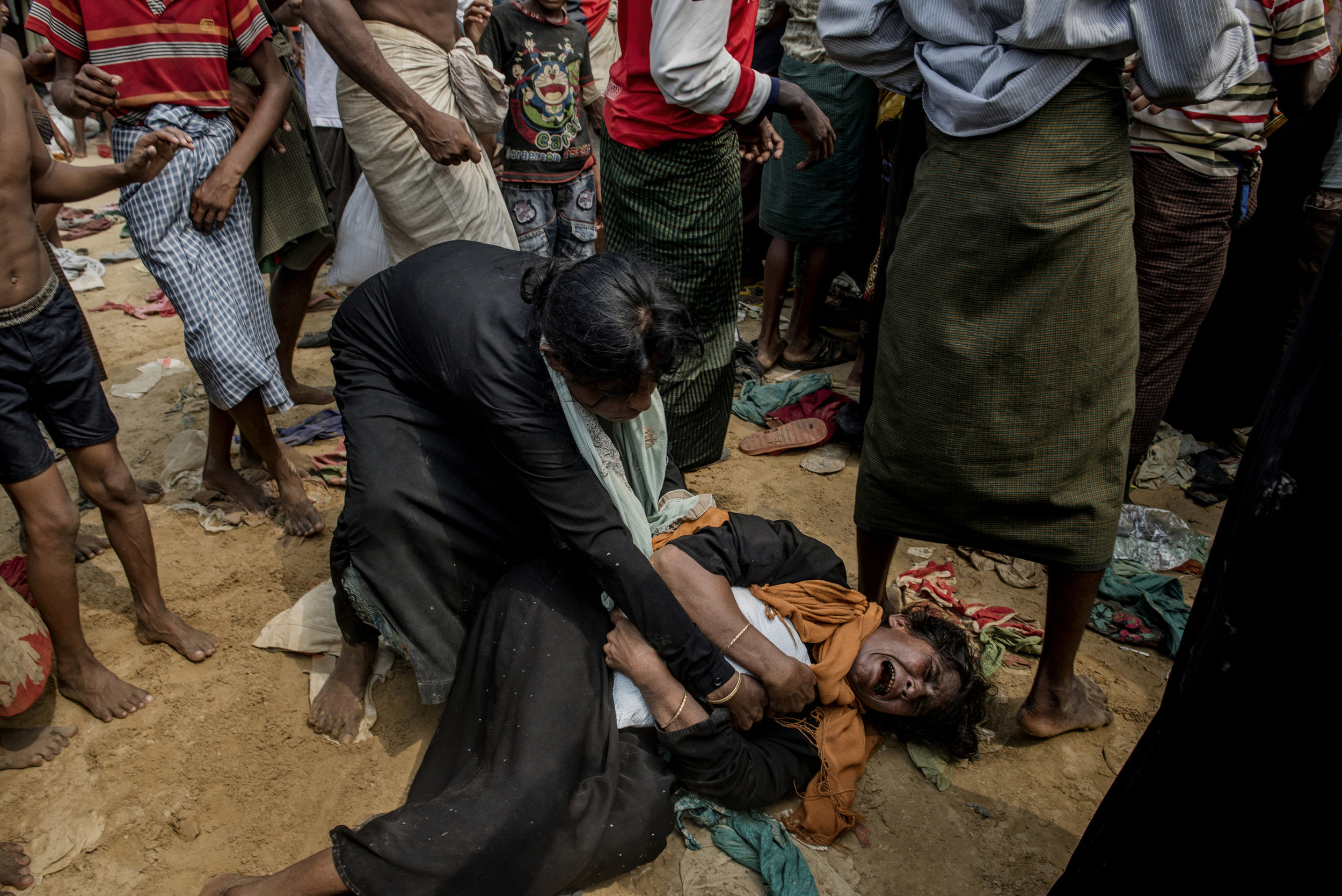 Two Rohingya women fight for a rack that was thrown from a truck with auxiliary shipments. There is a great lack of food and supplies in refugee camps.Edit