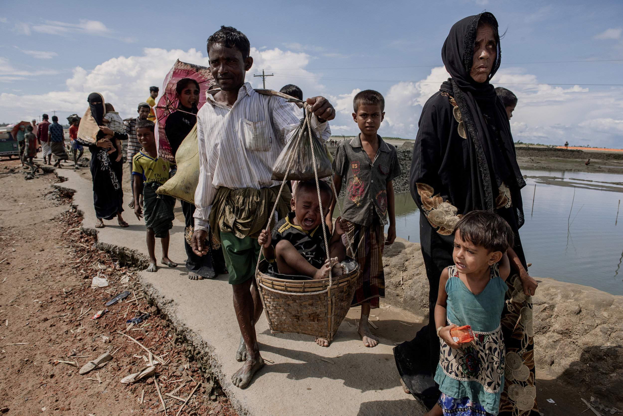 COX'S BAZAR, BANGLADESH- SEPTEMBER 13:  Saiful Rahman, 30 (white shirt) walks towards Teknaf mainland with his family after crossing the Naf river from Myanmar.