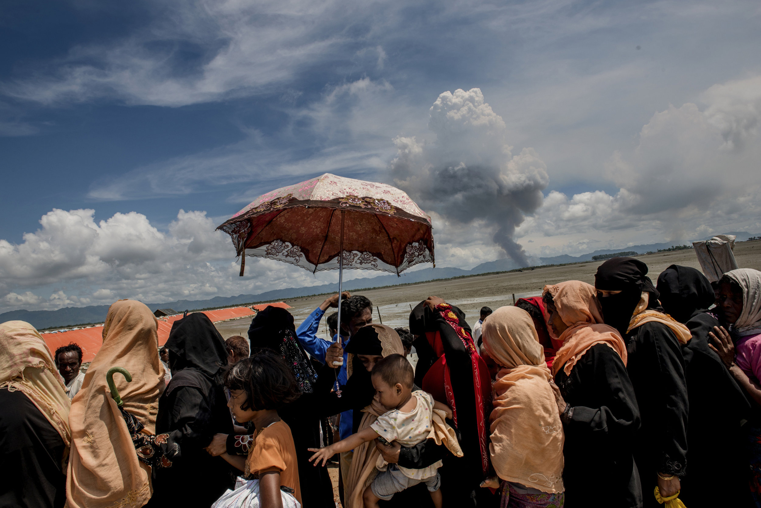 Rohingya refugees are waiting to get some relief at Shahporir Dwip on the border of Bangladesh and Myanmar. Smokes from burning villages visible on the horizon.