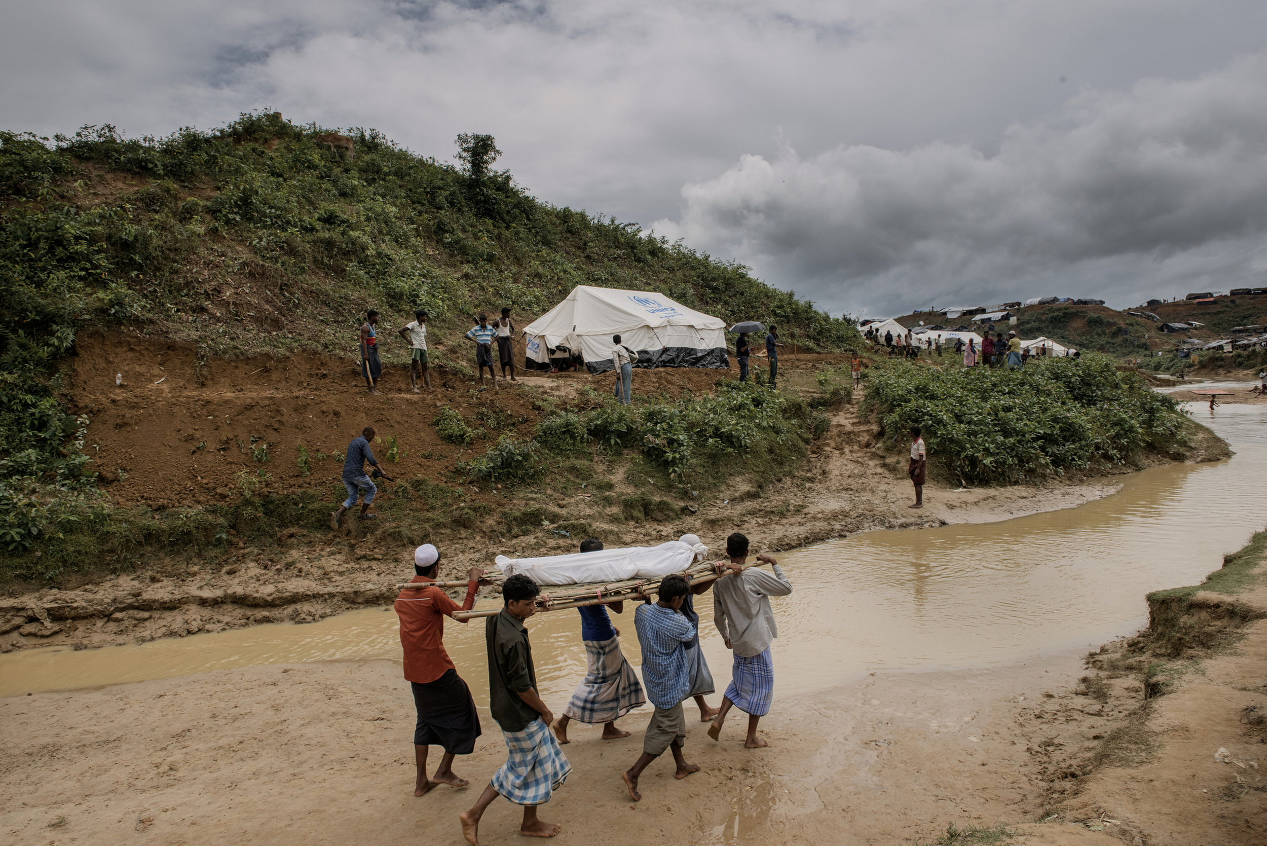 Rohingya refuges are cutting the trees and building the camps in the hilly forest, which used to wild elephants territory -  Last night around 11pm, a new Rohingya family (arrived 6 days ago in Bangladesh ) with 9 members were sleeping in extended part of Kutupalang registered camp, were attacked by a group of wild elephants, 2 people died rest of the people are in the hospital. In 2 dead people the older person was 45 years old and a baby, who was 8 months old. In this picture relatives taking the dead body of 45 years old to the makeshift cemetery.