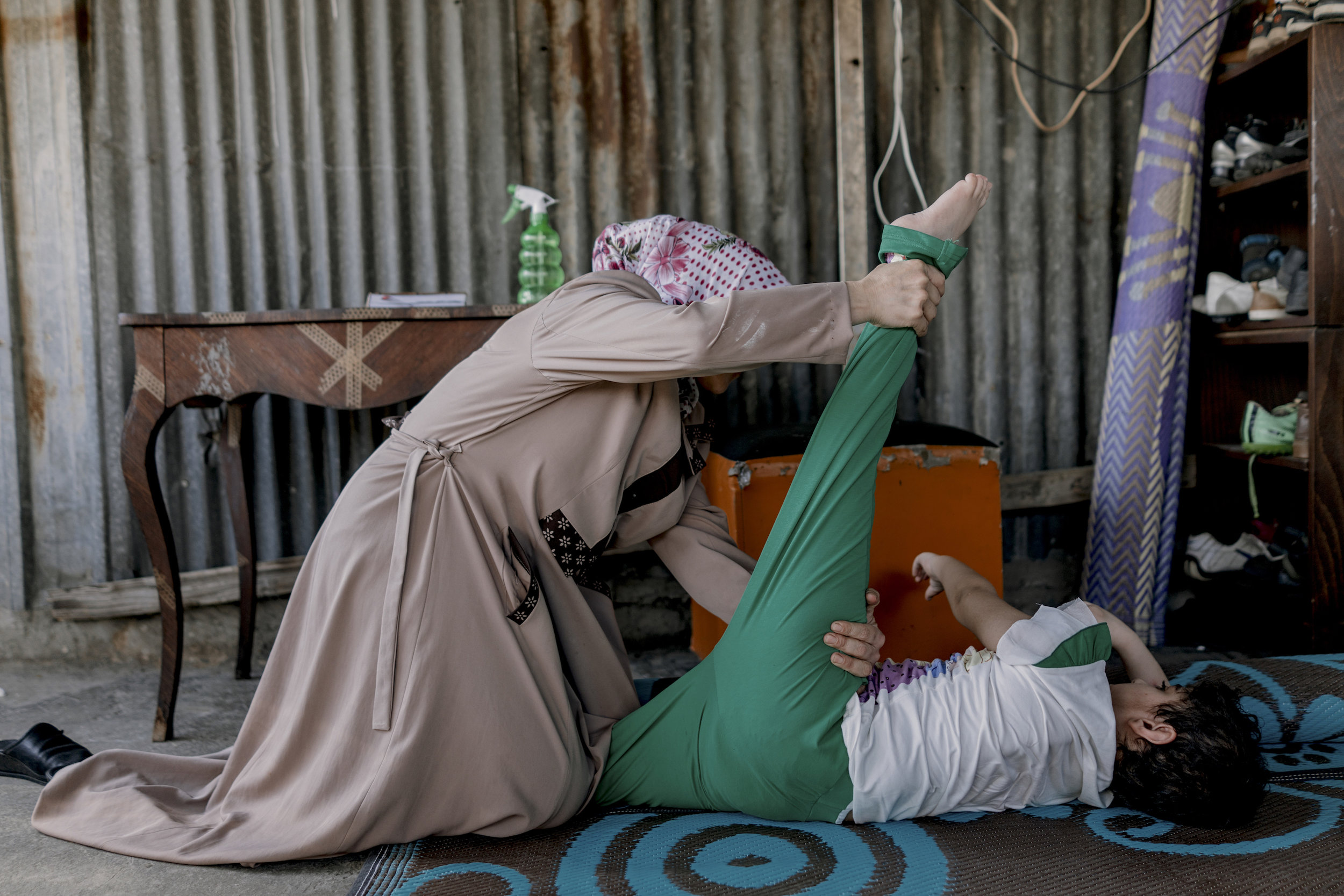 Leila El Saho gives physiotherapy to her daughter Sendos El Saho (12 years old). They live on the roof of an industrial building and they are composed of 7 members. Sindos is a girl suffering from a severe degree of cerebral palsy and epilepsy.