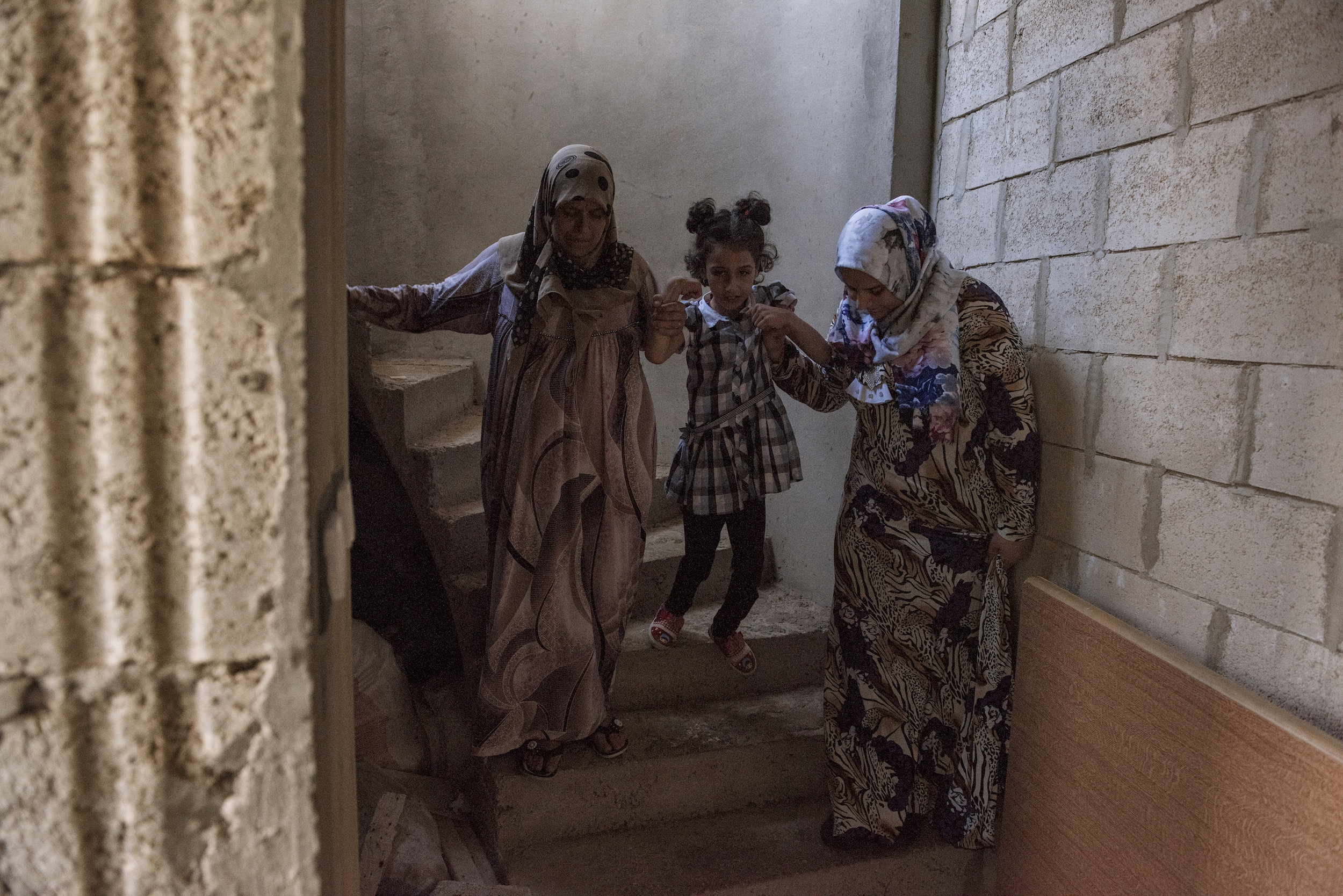 Fatima tries to walk with he help of her grandmother and her aunt in a their apartment in the outskirt of Mount Lebanon in Lebanon.