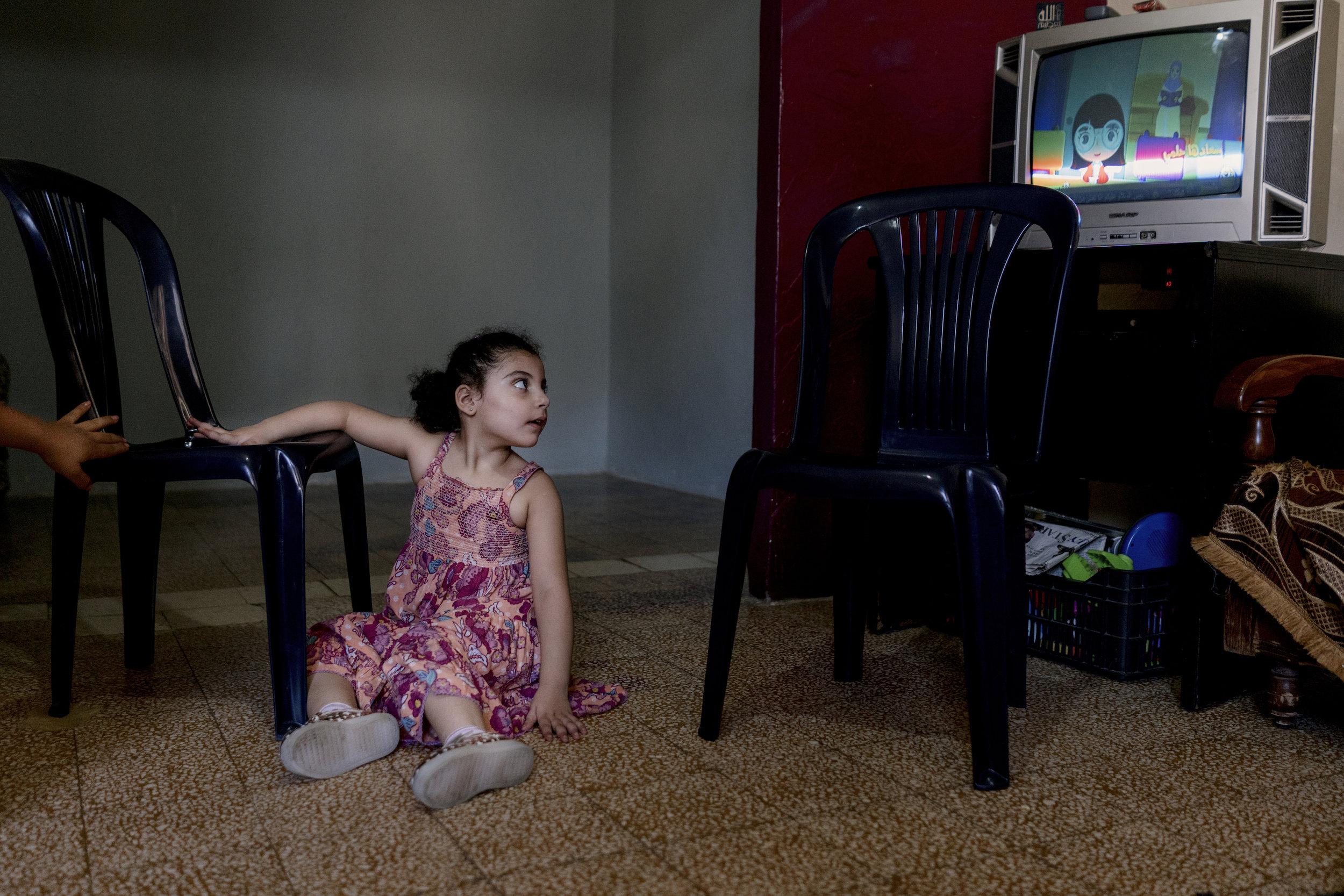 Khadijah watches TV in her small apartment in Beirut.Khadijah Moussa (6 years old) comes from a Syrian family composed of 7 members. They moved to Lebanon 5 years ago during the Syrian crisis for protection and survival. Khadija is one of 5 children, aged 6 years old and physically disabled.