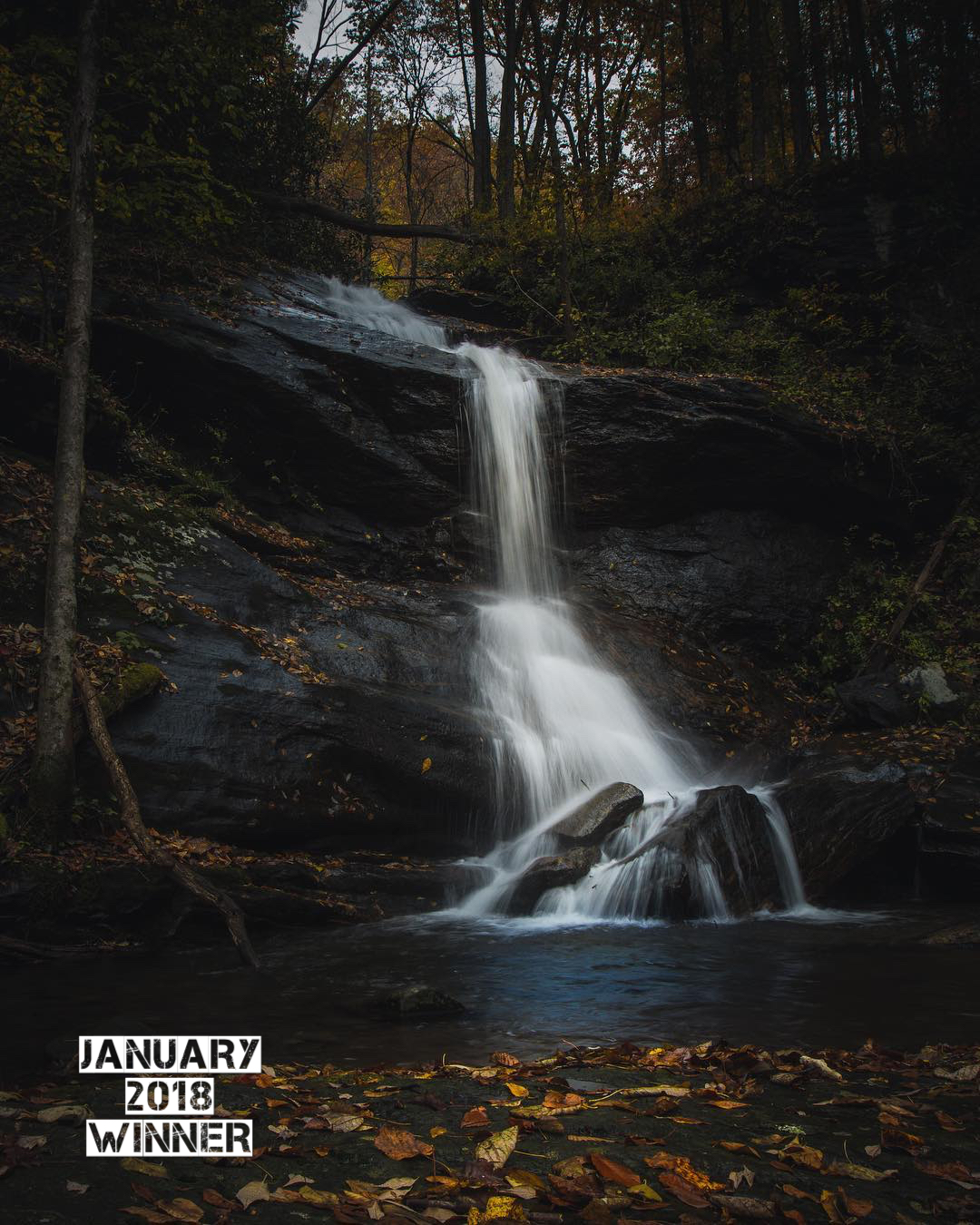 "Josh Wolf  is the winner of the January 2018 G.O. Photo Contest! January's theme was ""Smooth Water"" and Josh you nailed it with this awesome waterfall capture. The judges loved the juxtaposition of the white smooth water and the deep dark rocks, and then that pop of color in the fallen leaves on the foreground sent it over the top. they also loved the composition of this image. The top of the falls landing in the upper left focal point and the bottom of the falls landing in the lower right focal point. Also the way you have the light of the sky balanced out by the brightly colored leaves. When someone says you have ""an eye"" for photography, They are basically saying you have a natural understanding of composition. they just say ""an eye"" because it is shorter. HaHa. Great work Josh and thank you for sharing your amazing photography!"