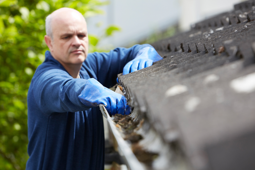 man cleaning home gutters