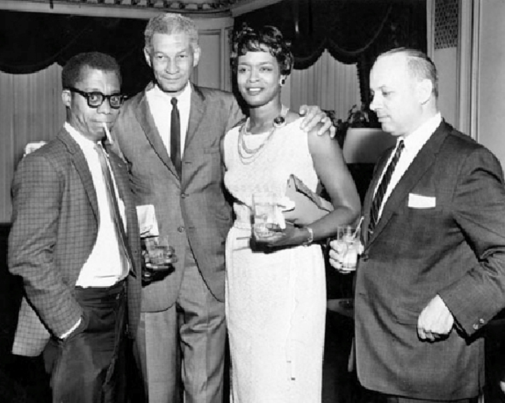 (l to r) James Baldwin, Chicago Urban League Executive Director Edwin 'Bill' Berry, Doris Blueitt, and Urban League board member Hank Schwab at a 1963 dinner in Baldwin's honor for the benefit of the Congress of Racial Equality (CORE). Chicago Defender