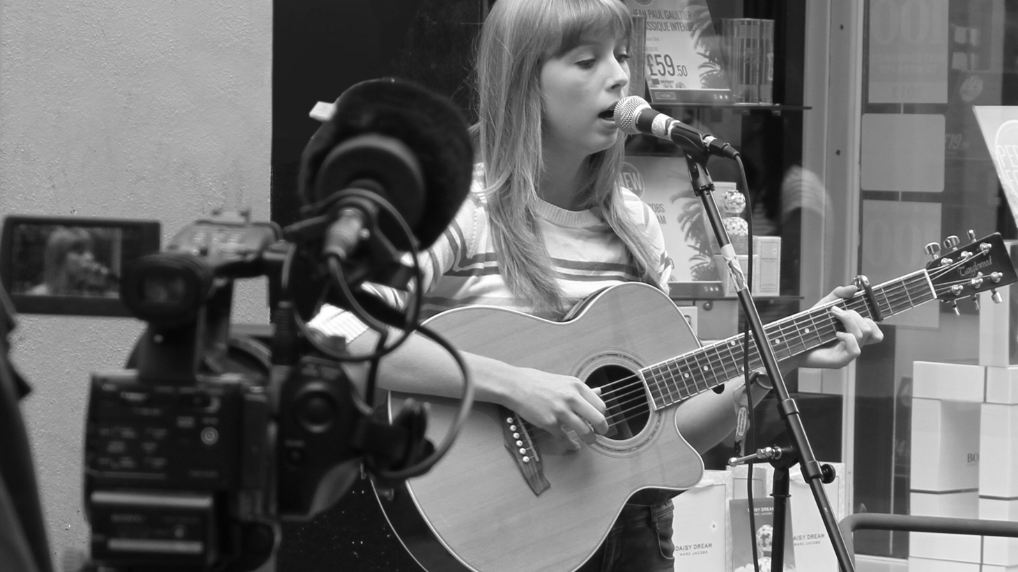 Mehalah Ray (Rachel Clark) being filmed by ITV News performing at the Cambridge Busking Festival