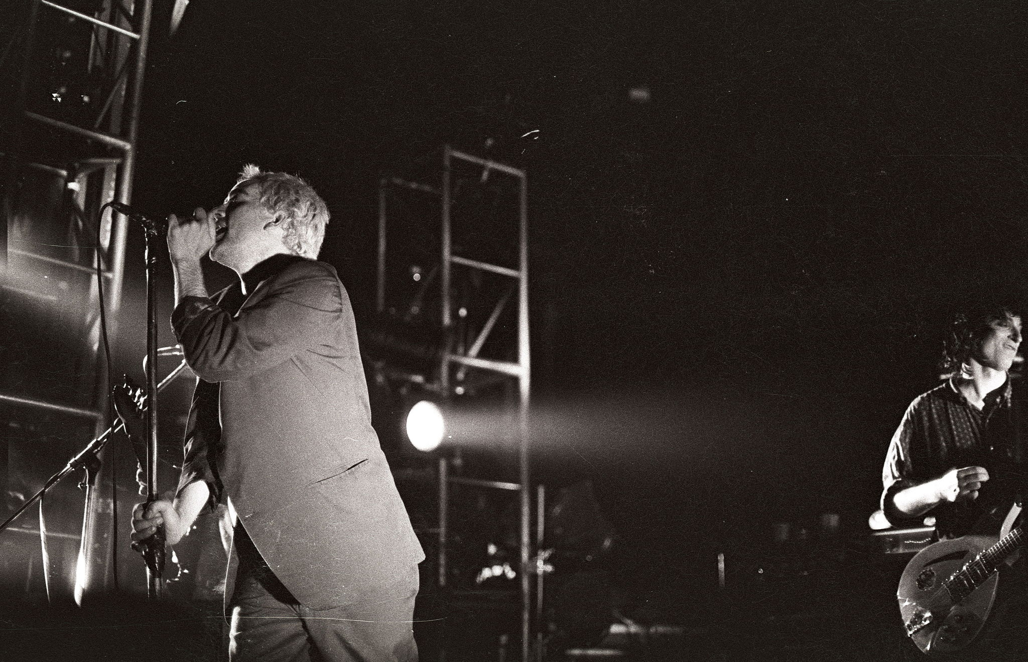 Michael Stipe (left) and Peter Buck (right) on stage in Ghent, Belgium, during R.E.M.  '   s 1985 tour.  Wikimedia Commons .