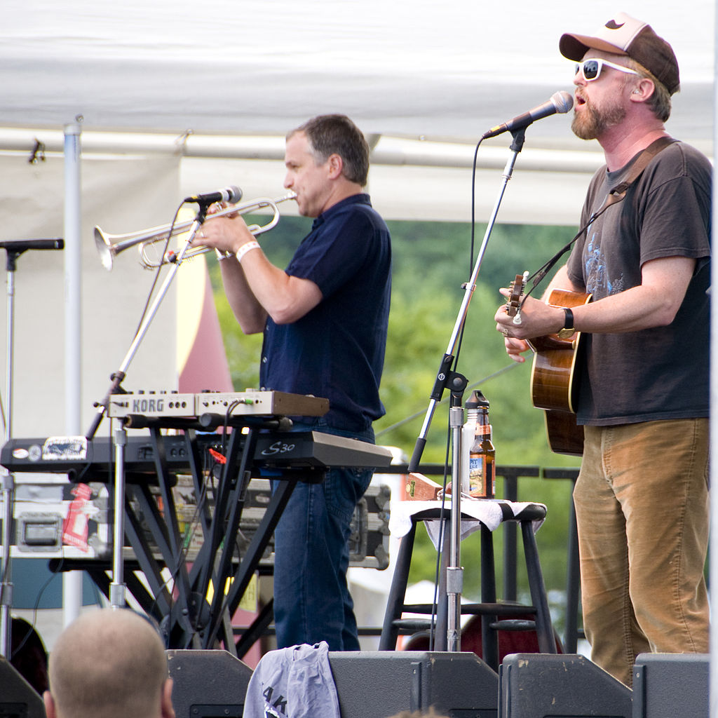 Cake performing in 2010. Vince DiFiore on trumpet, lead singer John McCrea on guitar. Image Credit: Jay Adan via  Wikimedia Commons .