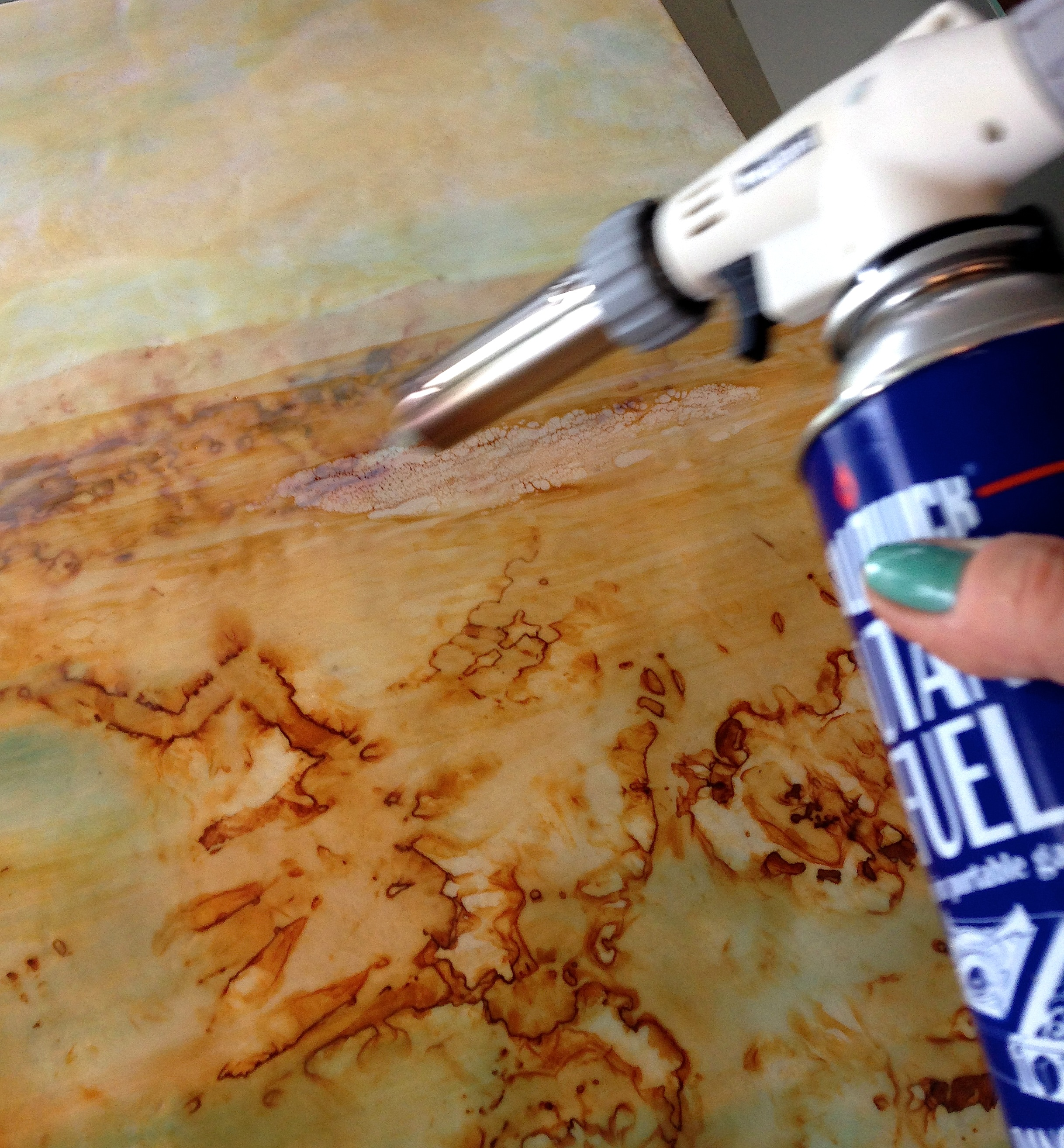 Using a butane torch to gently fuse a layer of wax over rusted silk, one of at least 12 layers in the process.