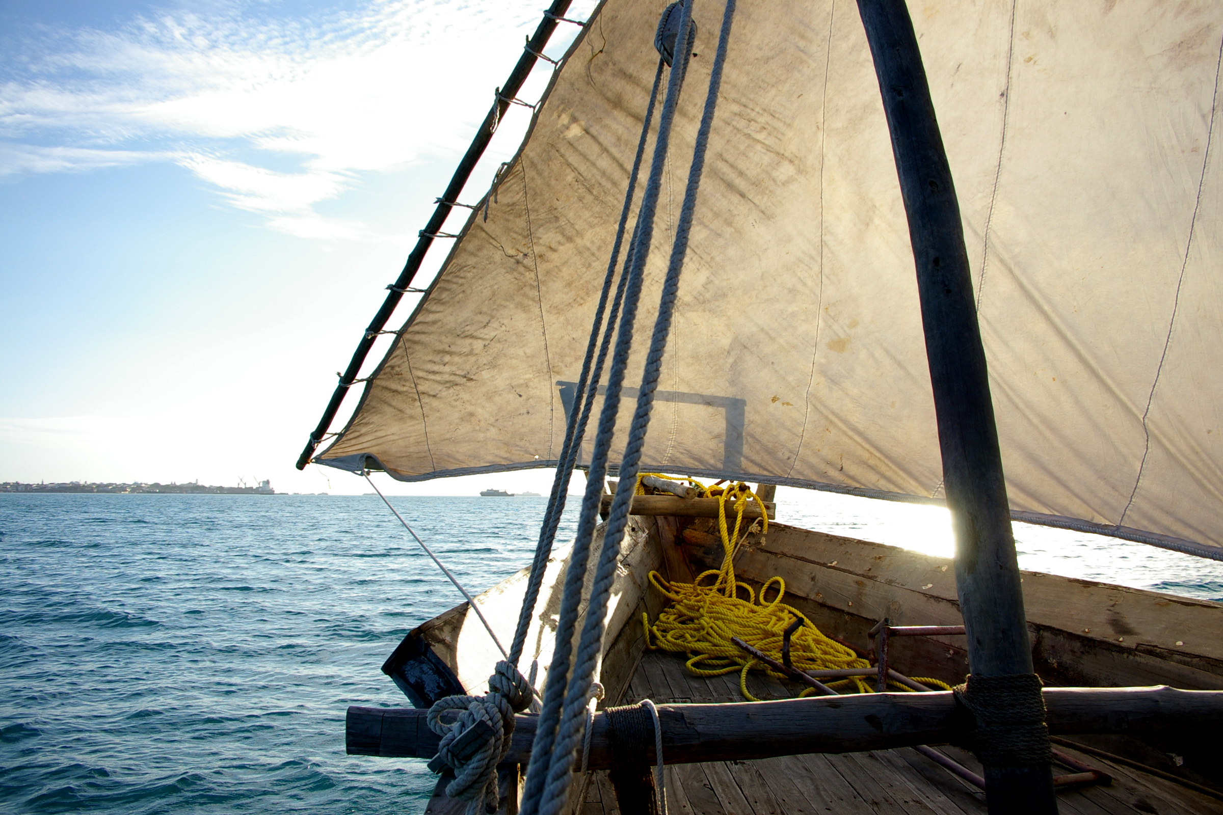 The bow of a dhou on a sunset sail along the shore