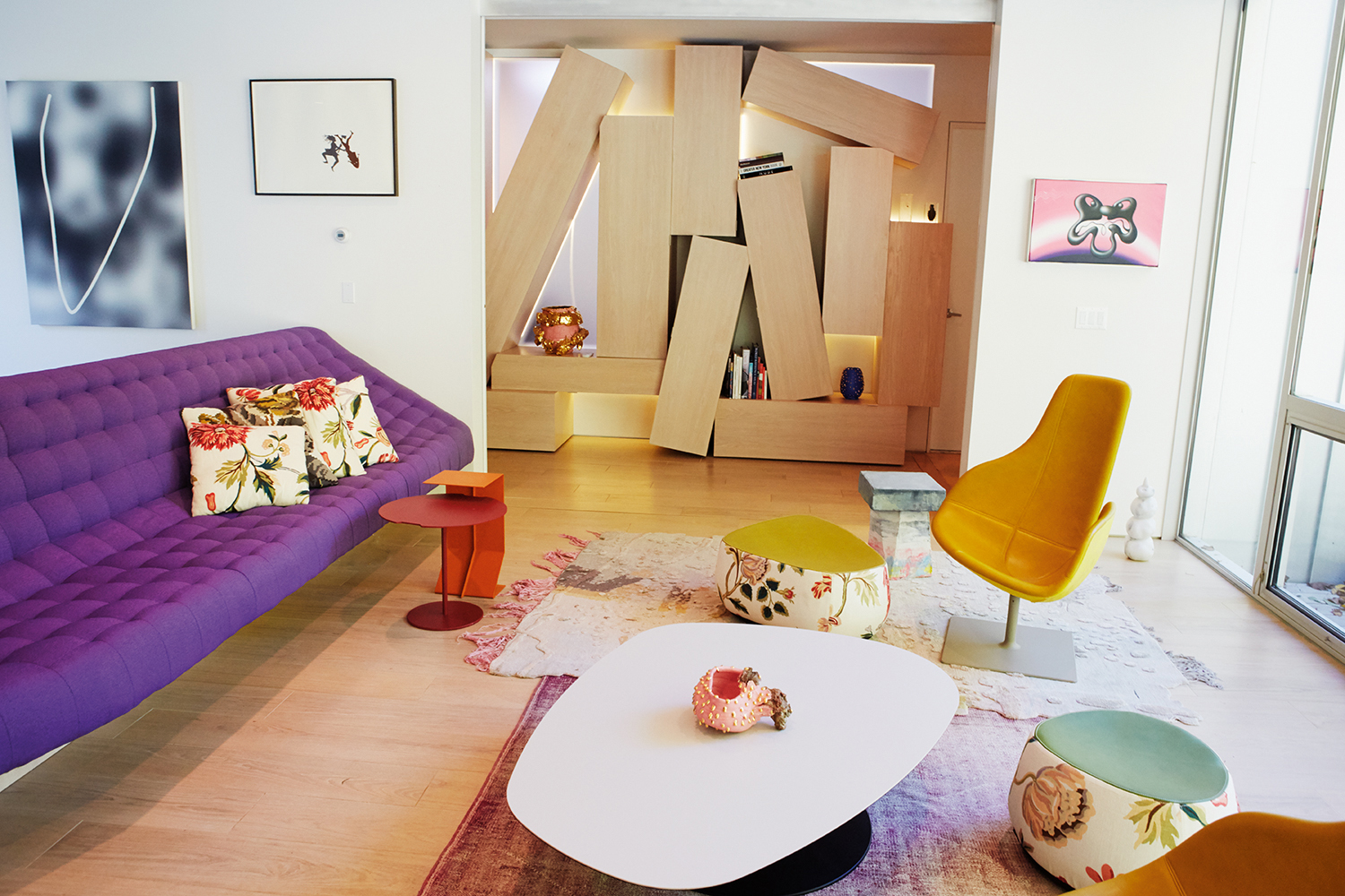 Artist on the living room wall: Jeff Elrod, Kara Walker and Kenny Scharf. Furnished with pieces by Anton Alvarez, Kueng Caputo and Patricia Urquiola. Jumble of boxes is a coat closet designed by their interior decorator  Giancarlo Valle .