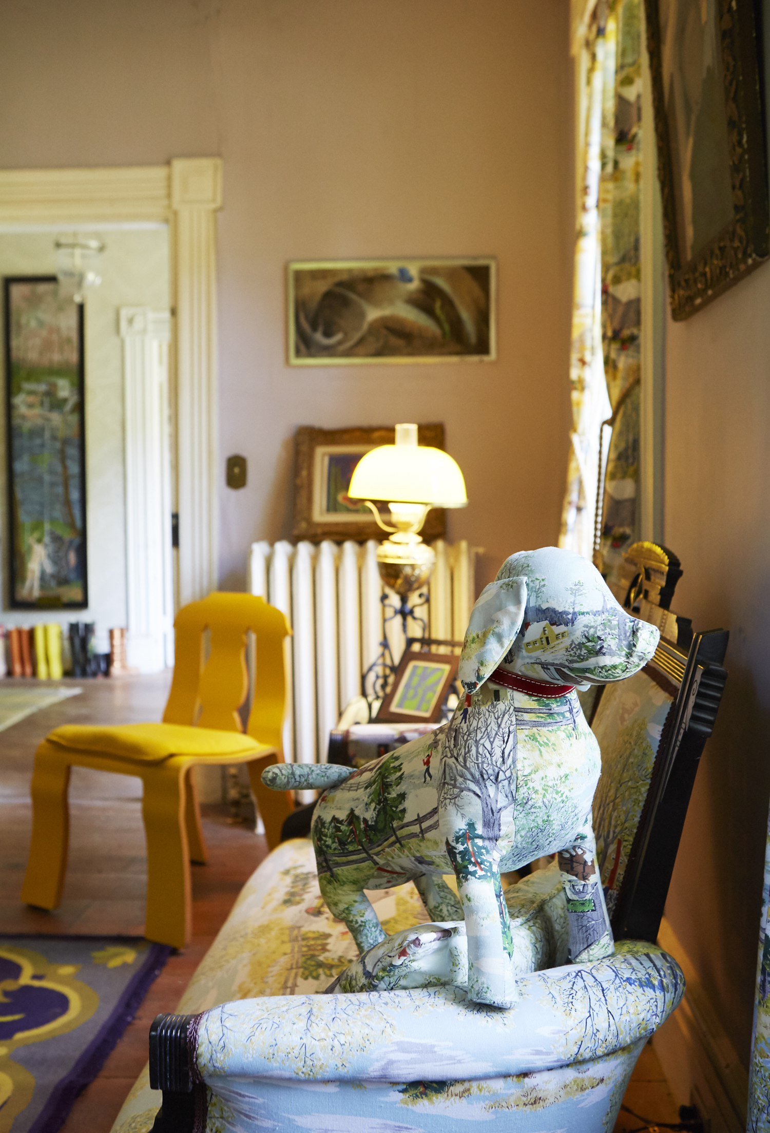 Empire  chair by Robert Venturi and Denise Scott Brown. Grandma Moses fabric  Doggie doll  pillow by Peyton Jefferson.