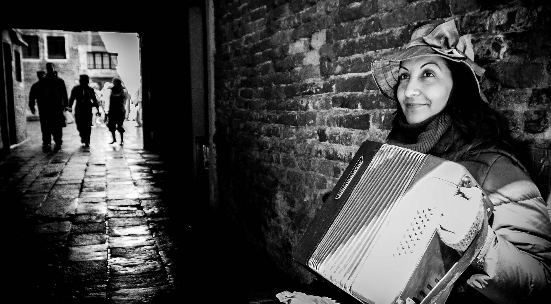I photographed this busker in the half light of an alley following a wet and windy morning in Venice.  The combination of the light, the wet cobbles and the people walking towards her makes a story and one unlikely to be photographed by others that day.