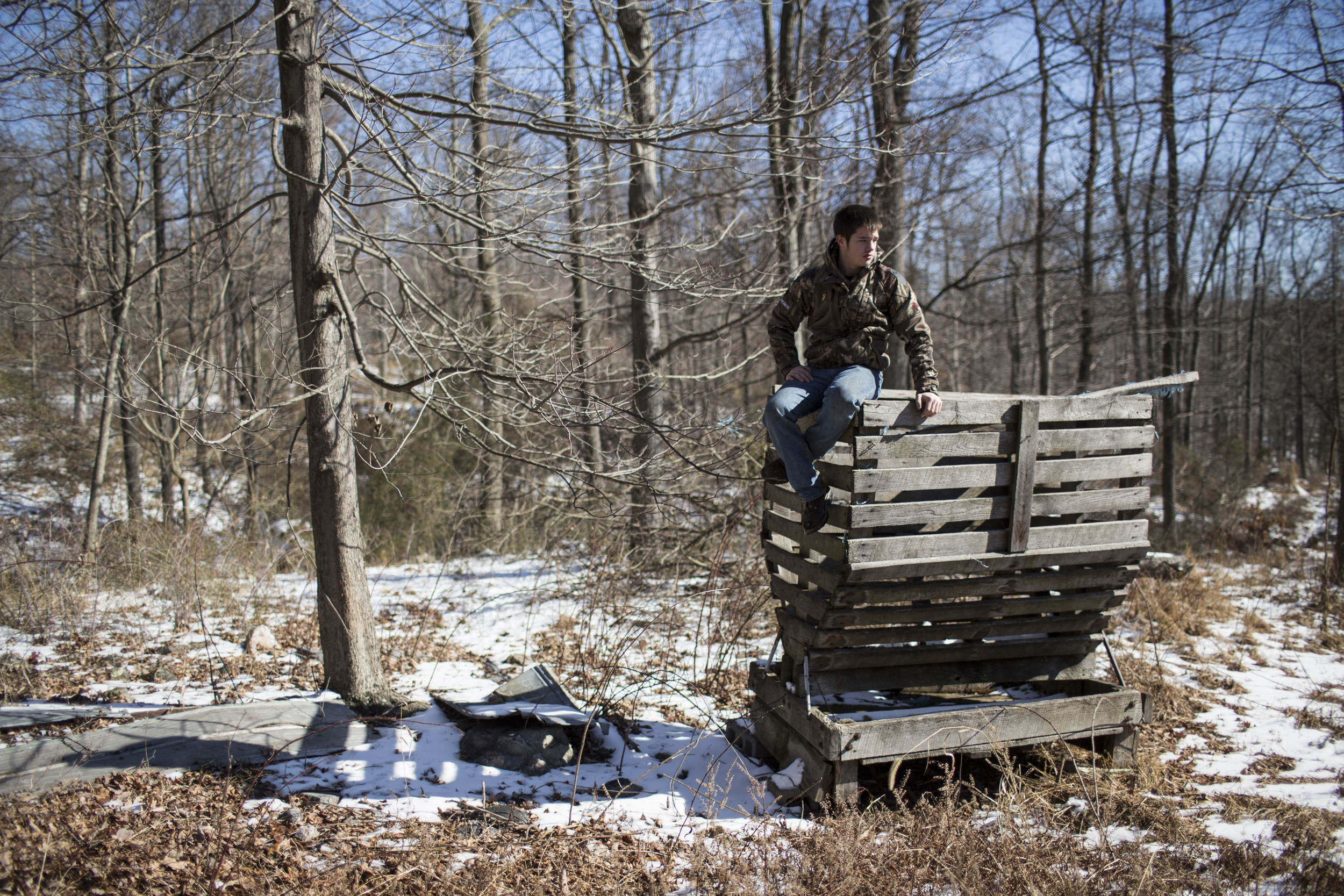 Hunter sits atop an old feeder during a winter work party at the Heartwood Outdoors hunting camp near Indian Springs, Maryland.