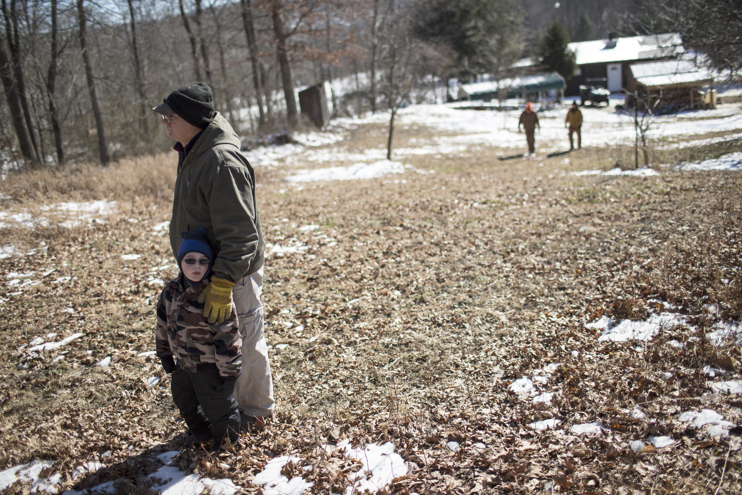 Dick stands with a young boy during a work party at the Heartwood Outdoors hunting camp near Indian Springs, Maryland.