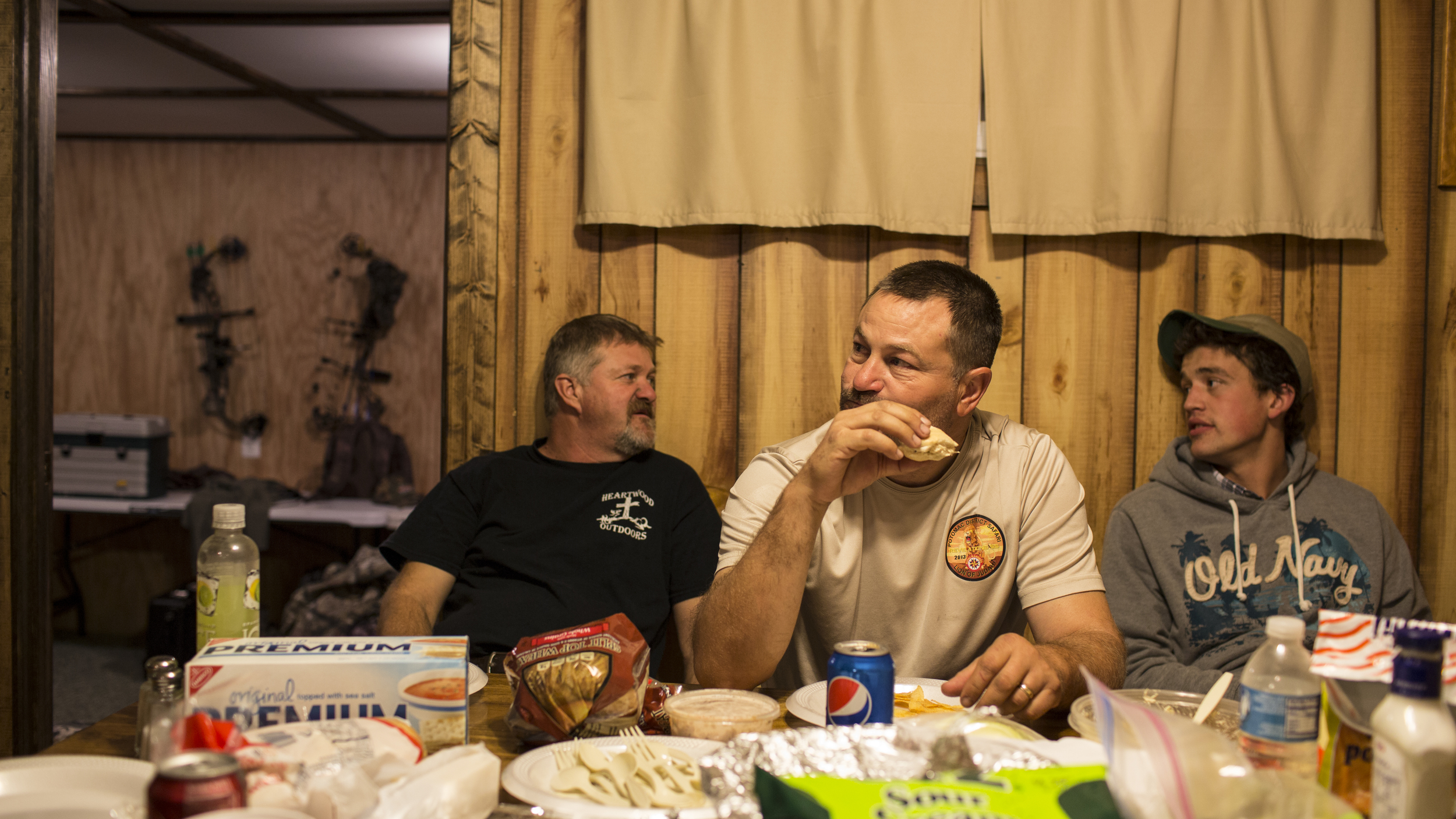 Tracy (L), his older brother Troy (C), and another hunter enjoy a evening meal after a hunt at the Heartwood Outdoors camp near Indian Springs, Maryland.
