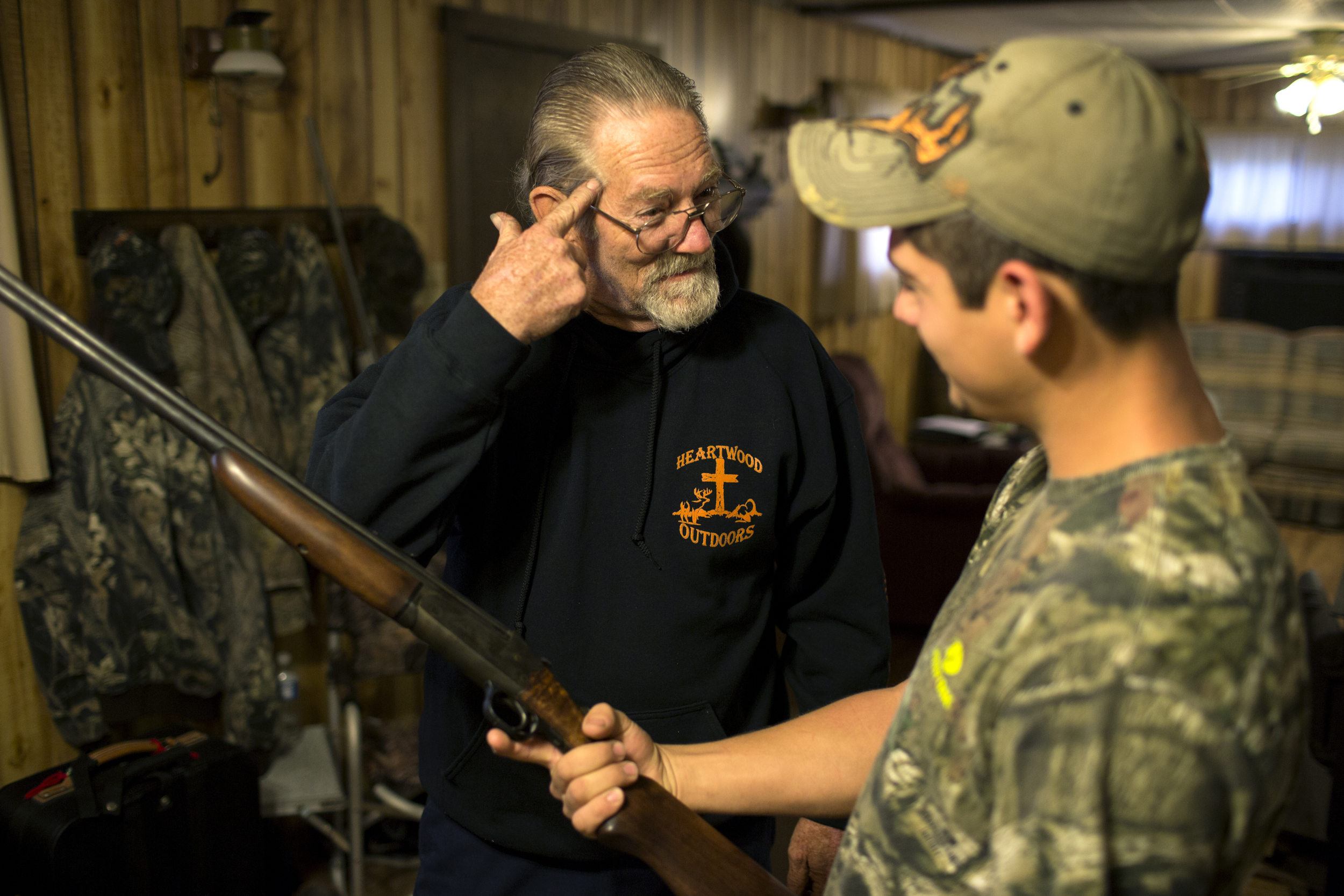 Doug explains to Dale the perks and efficiencies of hunting deer with a rifle rather than a bow at a hunting camp near Indian Springs, Maryland.