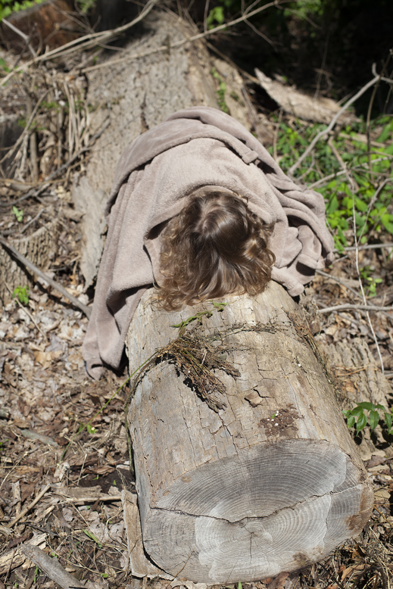 Isa on an Ash Trunk, 2018  In this image, my daughter Isa lies beneath a tan blanket on an Ash log that was felled after being infected by the Emerald Ash Borer. The Ash Borer has dramatically transformed the forest canopy around my childhood home, where Ashes once made up 20% of the tree population. The vulnerability of all living things to environmental changes seems particularly pronounced when looking at these once majestic trunks and their many age rings.