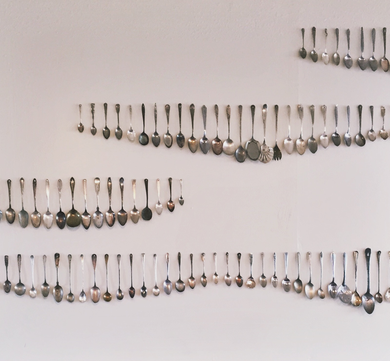 Spoons of all shapes and sizes arranged in lines on the walls of a nashville restaurant