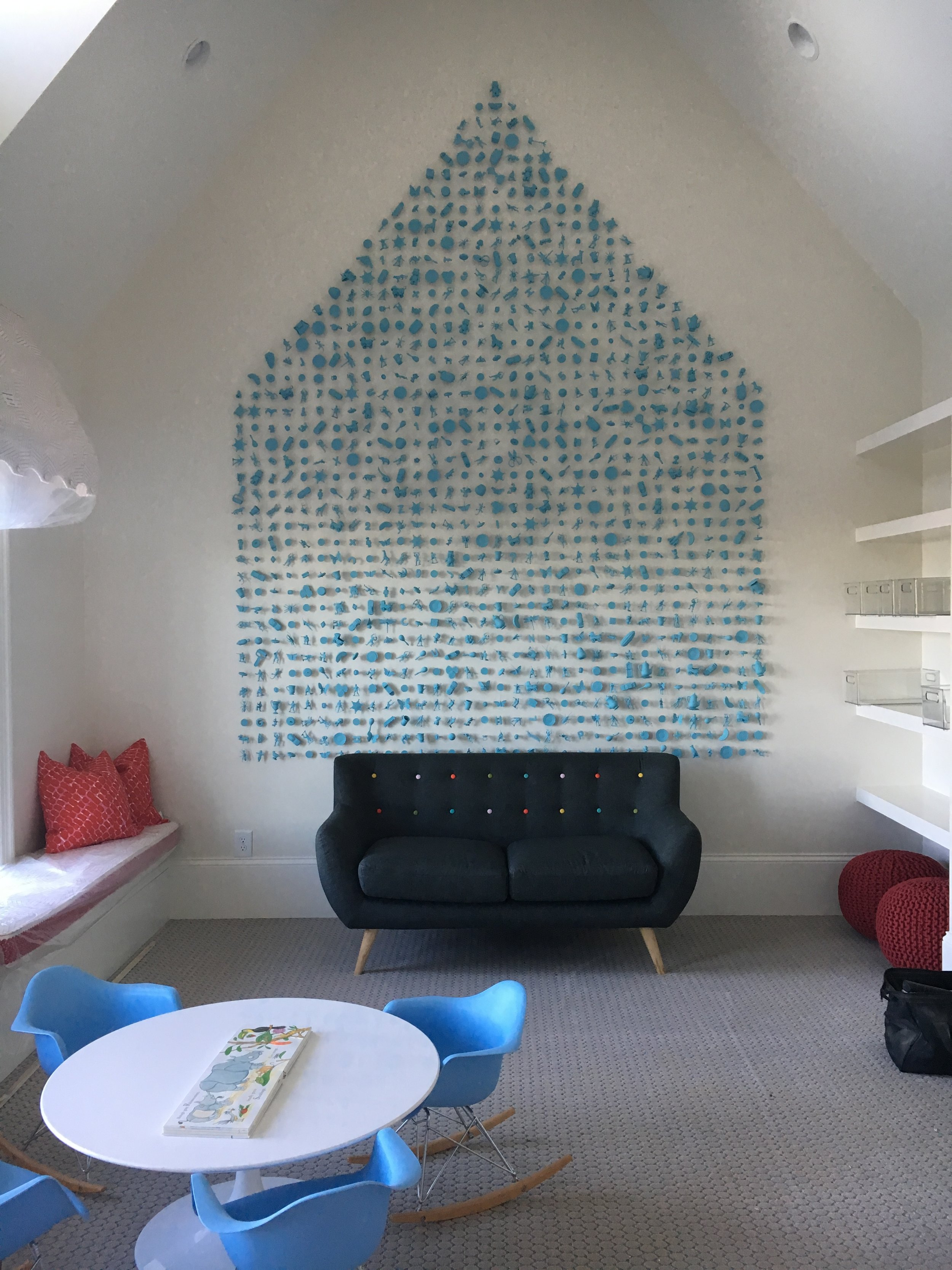 Thousands of toys, painted monochromatic blue, and assembled on the walls of this stunning playroom.