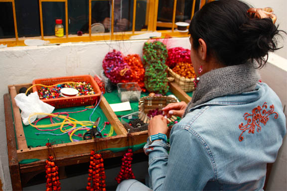 After the seeds and fruit are dried and painted, they are crocheted together according to any one of hundreds of designs, all by hand.