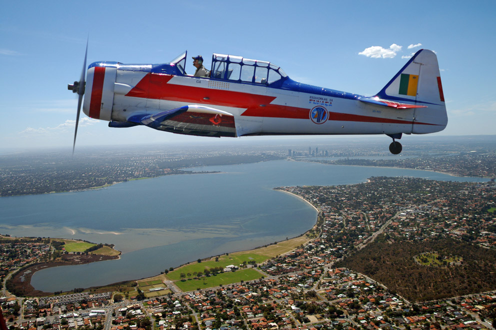 Rob Poynton flying his newly restored T6 over Perth WA. This is painted in the colours of the Brazilian Aerobatic Team