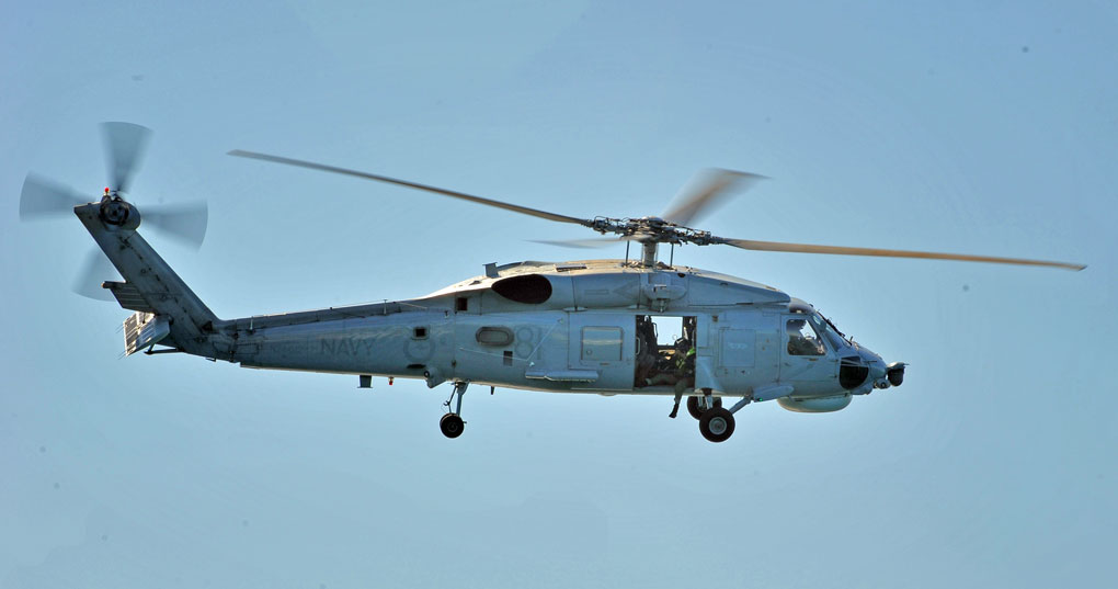 Jon leaning out of a Sikorsky S70B Seahawk helicopter