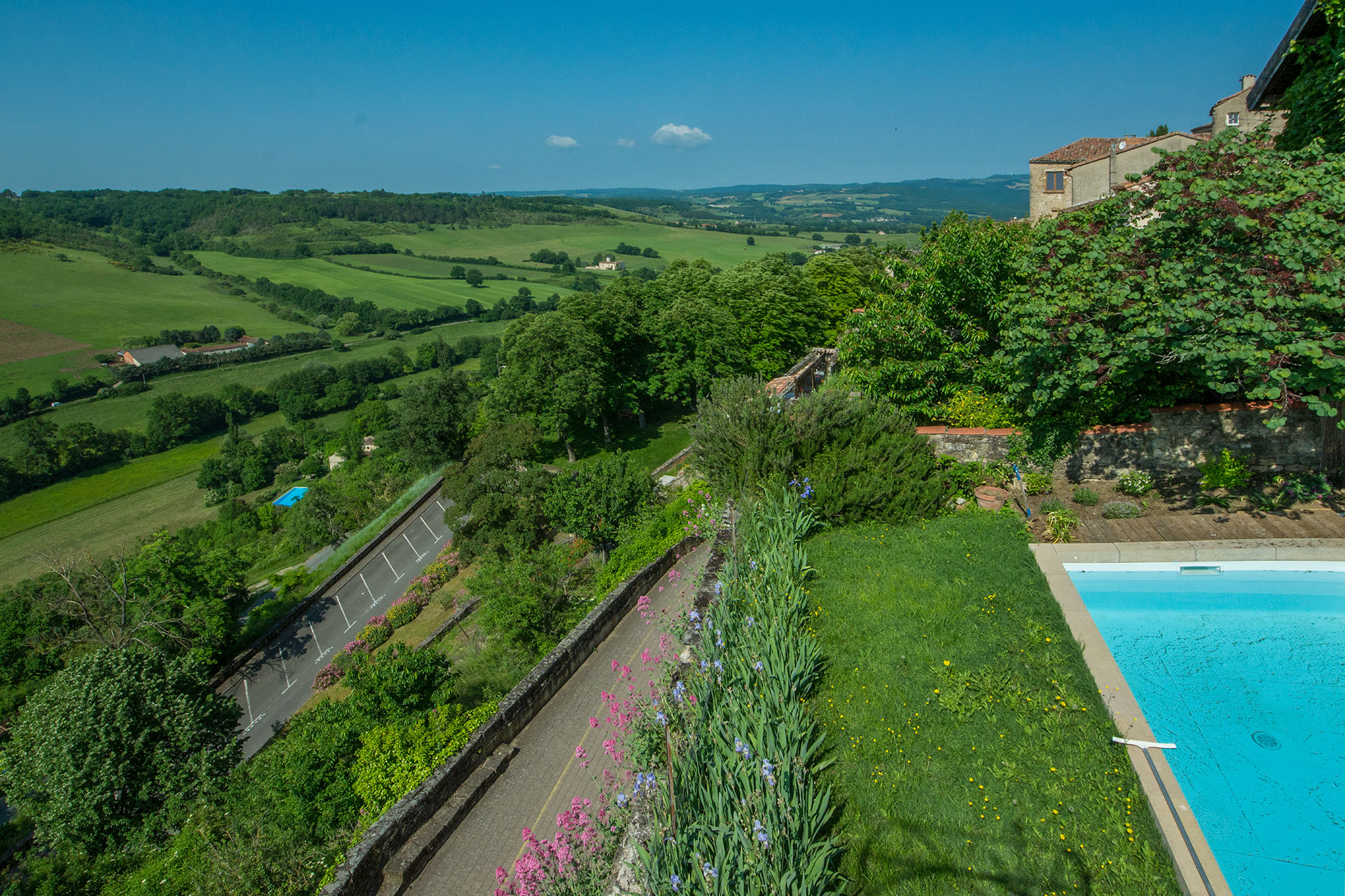 Our pool and garden, showing the proximity to the nearby Aurosse valley. The lower road (with parking lines) is the only road to the top of the medieval village, or Le Cite. Taken May 2018.