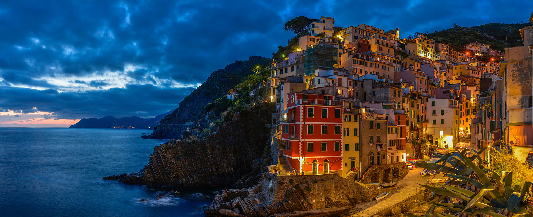 Dusk panorama of Riomaggiore. The lights of Monterosso are visible in the distance.