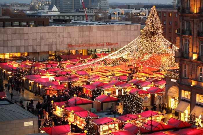 """ Christmas Market at the Cologne Cathedral 2011 "", ©  Superbass   /  CC-BY-SA-3.0  (via Wikimedia Commons)"". Street markets such as the ones typical of Germany, Austria, and surrounding places usher the holiday forth with hot mulled wine, good regional food, ornaments, toys, and spirit."