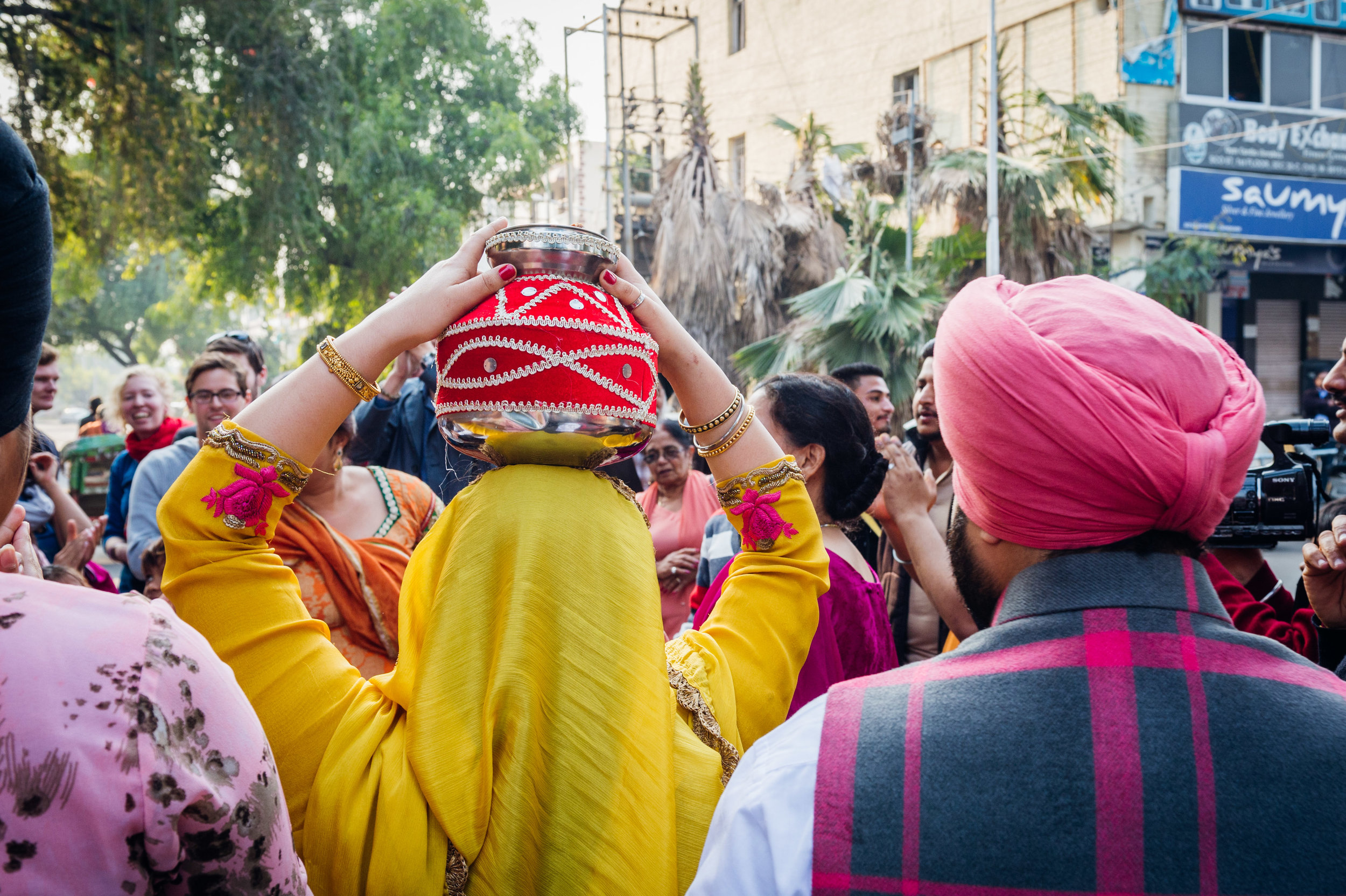 A female relative carries the Gharoli on her heading walking towards the Gurudwara.