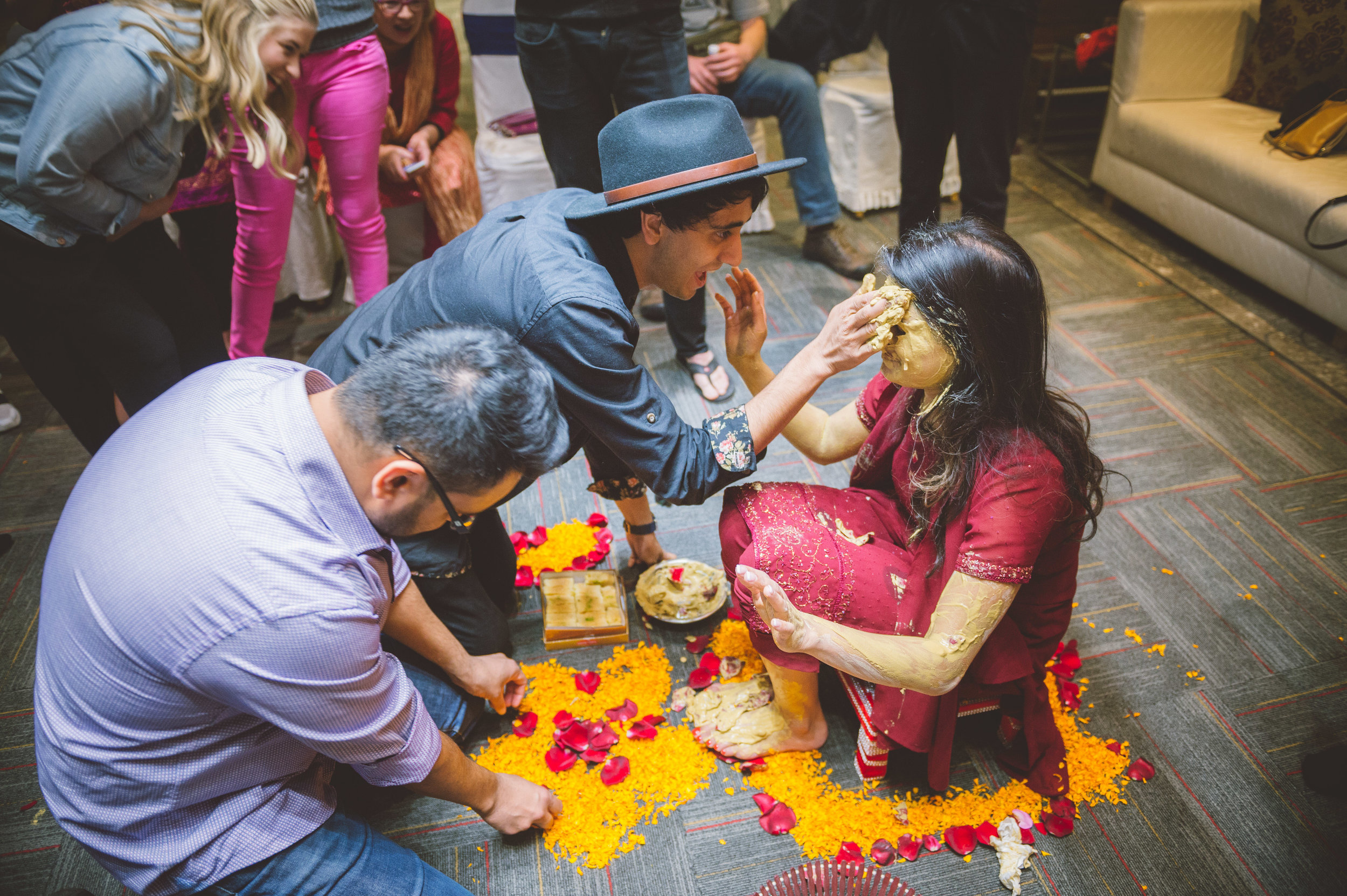The bride's youngest brother putting a good amount of turmeric paste on his sister's face.