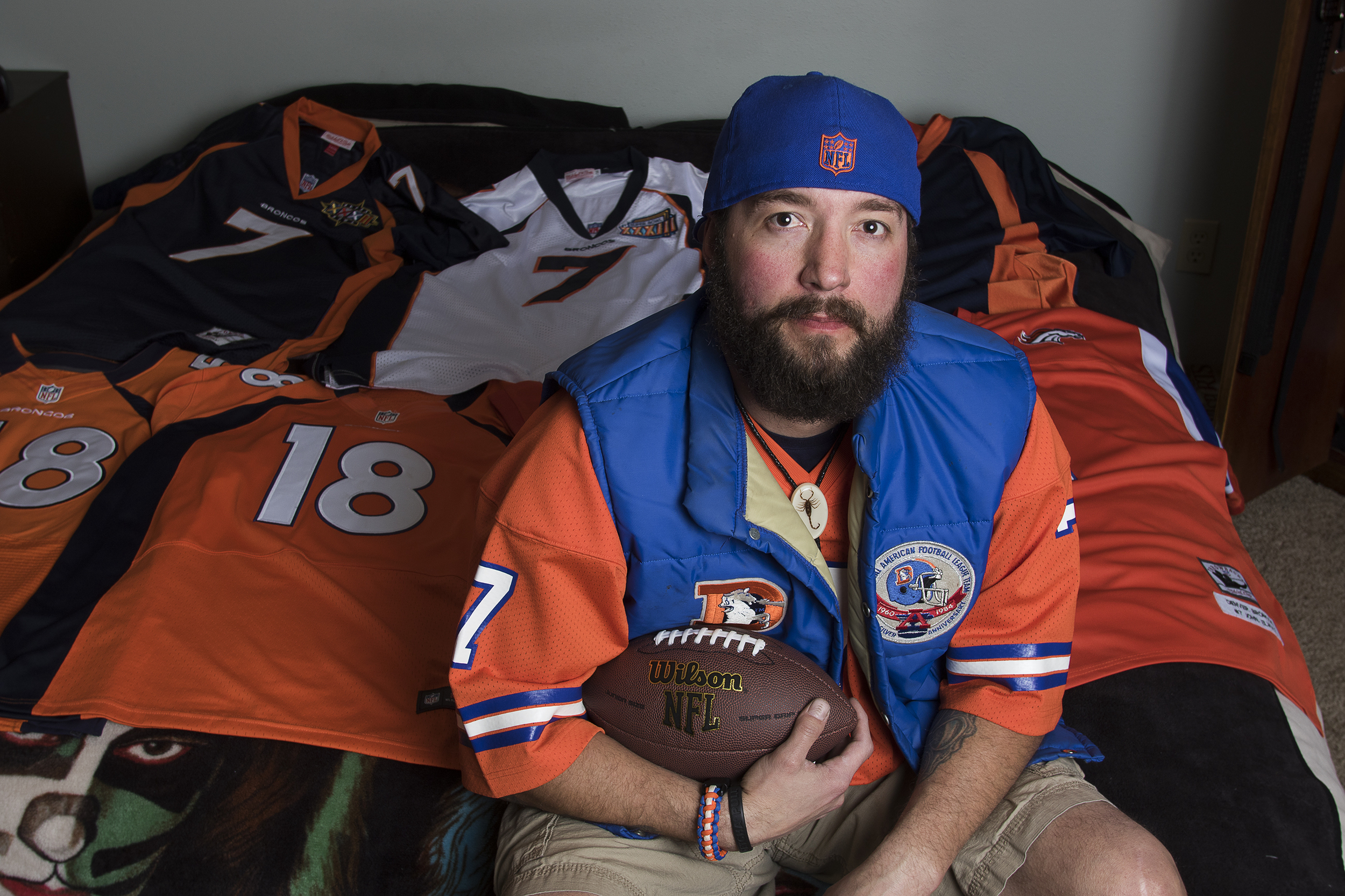 Jeremy Geiser sits on his bed with a selection of his 25 different Broncos jerseys Thursday evening. Geiser also owns at least 50 Broncos hats, a Broncos laundry basket, razor, and a model of some of the 1998 Broncos team, including his favorite Bronco, John Elway.