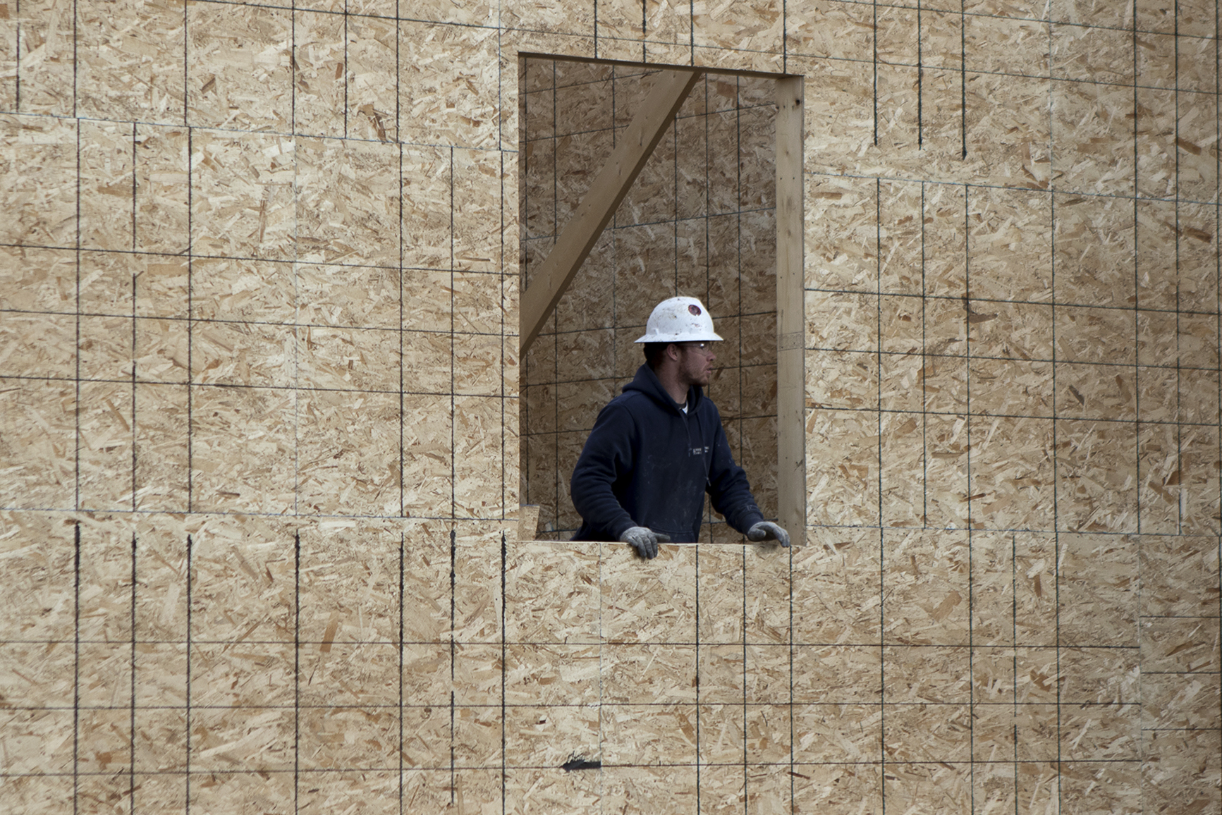A worker with Van Ewing Constructions talks to another crew member through a window Wednesday afternoon at while working on the new dorms at Gillette College.