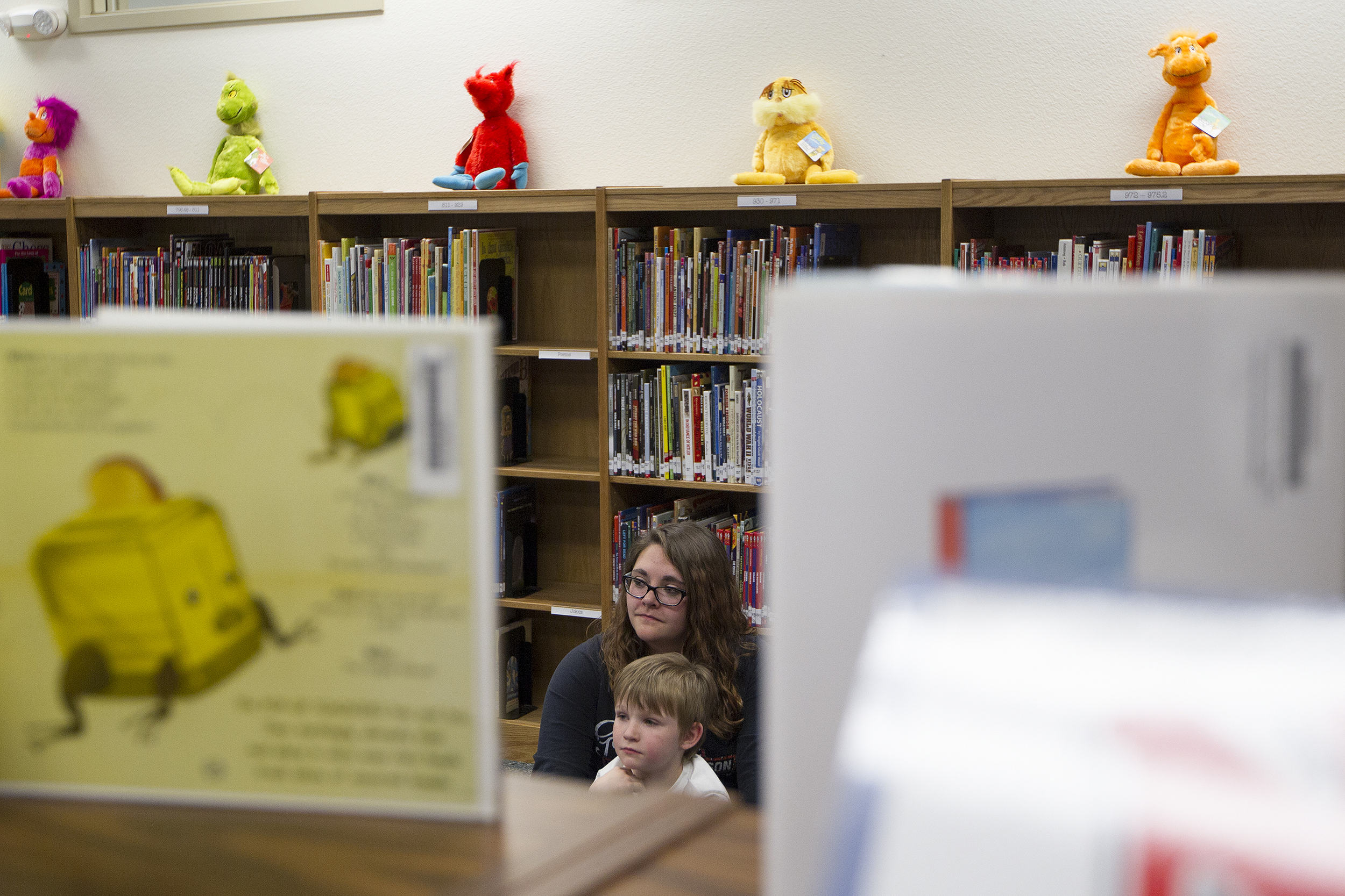 Kinsley Switzer, 14, and her brother Harlen Serrano, 5, listen to Cloud Peak Energy's Luke Malyurek read a book during Eat, Read, Grow Tuesday night at Wagonwheel Elementary School. Eat, Read, Grow is a program rotating around different schools where volunteers visit with kids, read to them, and the kids and get to take home a new book and a bag of groceries.