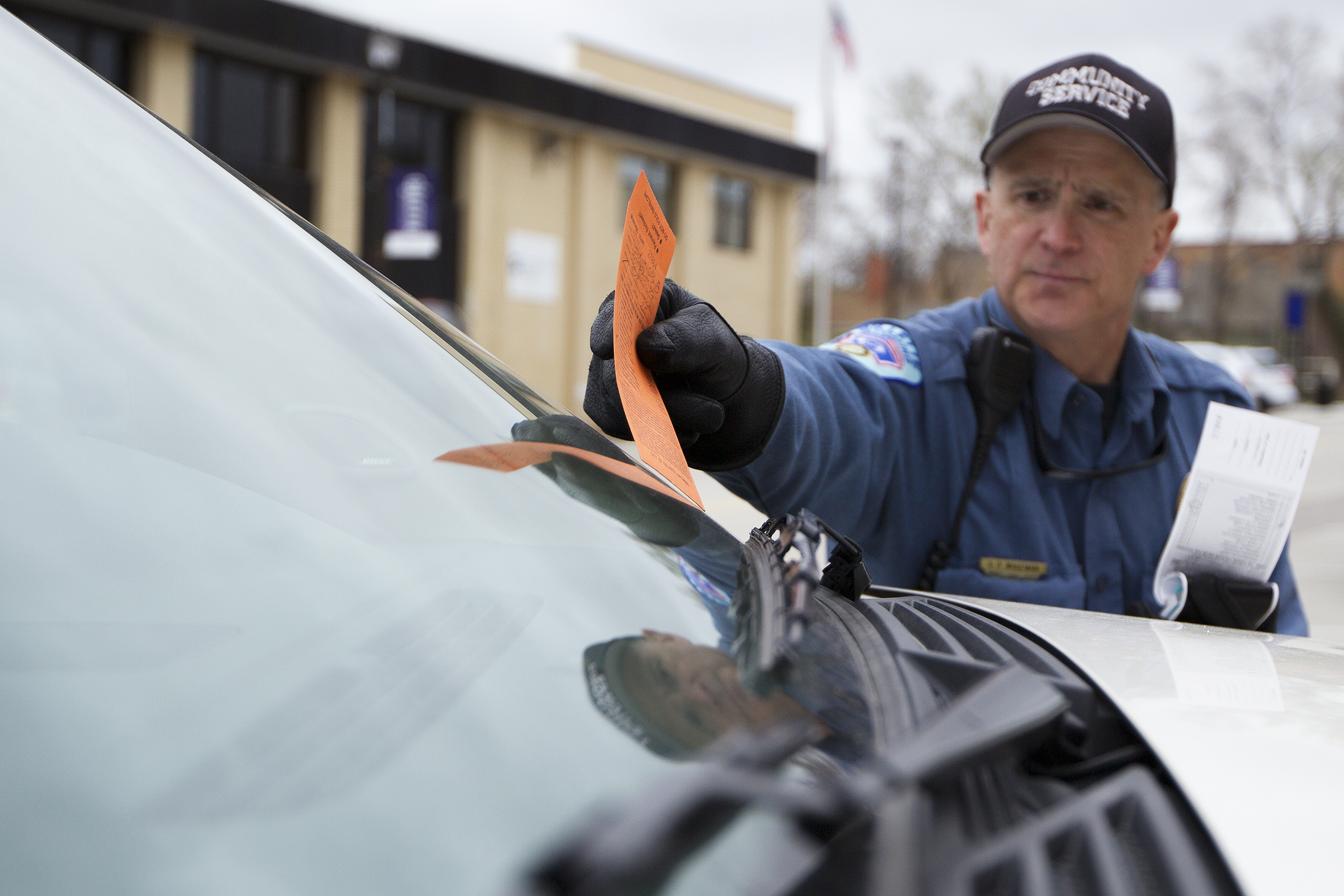 Gillette Community Service Officer Steve Wageman places a parking ticket on the windshield of a car on Gillette Avenue Tuesday afternoon. The city is hoping to cut between $450,000 and $500,000 by only filling two of the currently, or soon to be, open positions in the department.