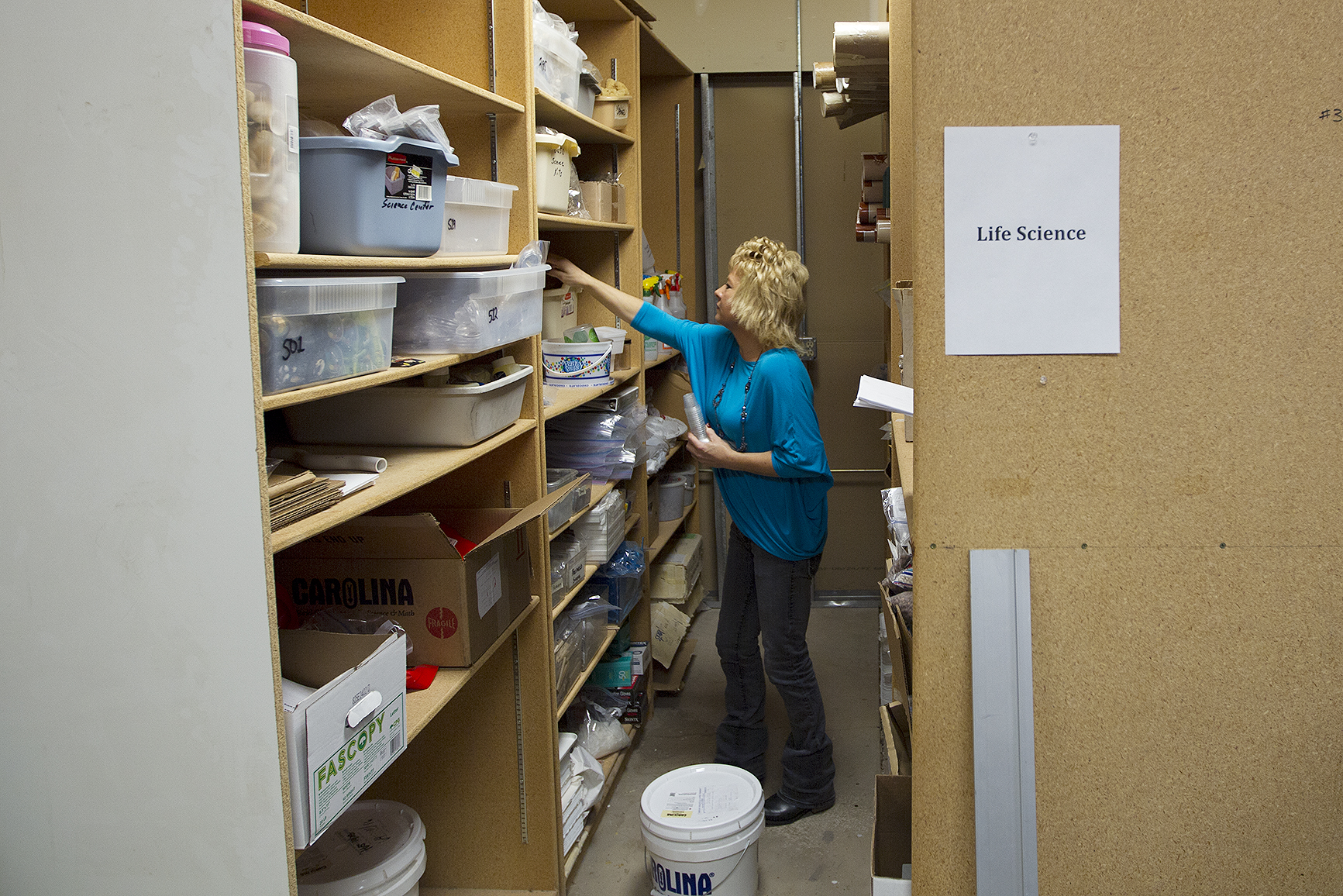 "Science Center Technician Candy Morgan collects materials Friday morning for a science kit that she's prepping for next fall. Once the kits get used and returned, Morgan goes through them and refills any materials that are needed, and repairs anything that's broken or worn out. ""A lot of the new ones, we test them and make sure that they work,"" before sending them out to the classrooms she said."