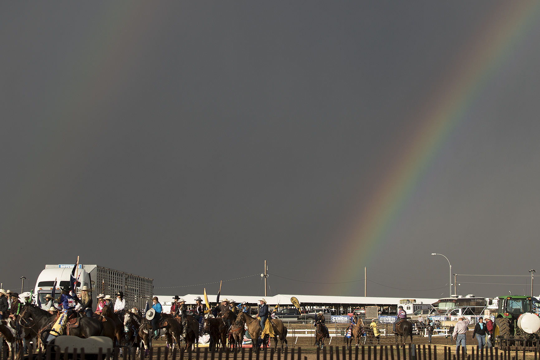 Contestants prepare for the start of the first performance of the National High School Finals Rodeo Sunday evening under a double rainbow at Morningside Park.