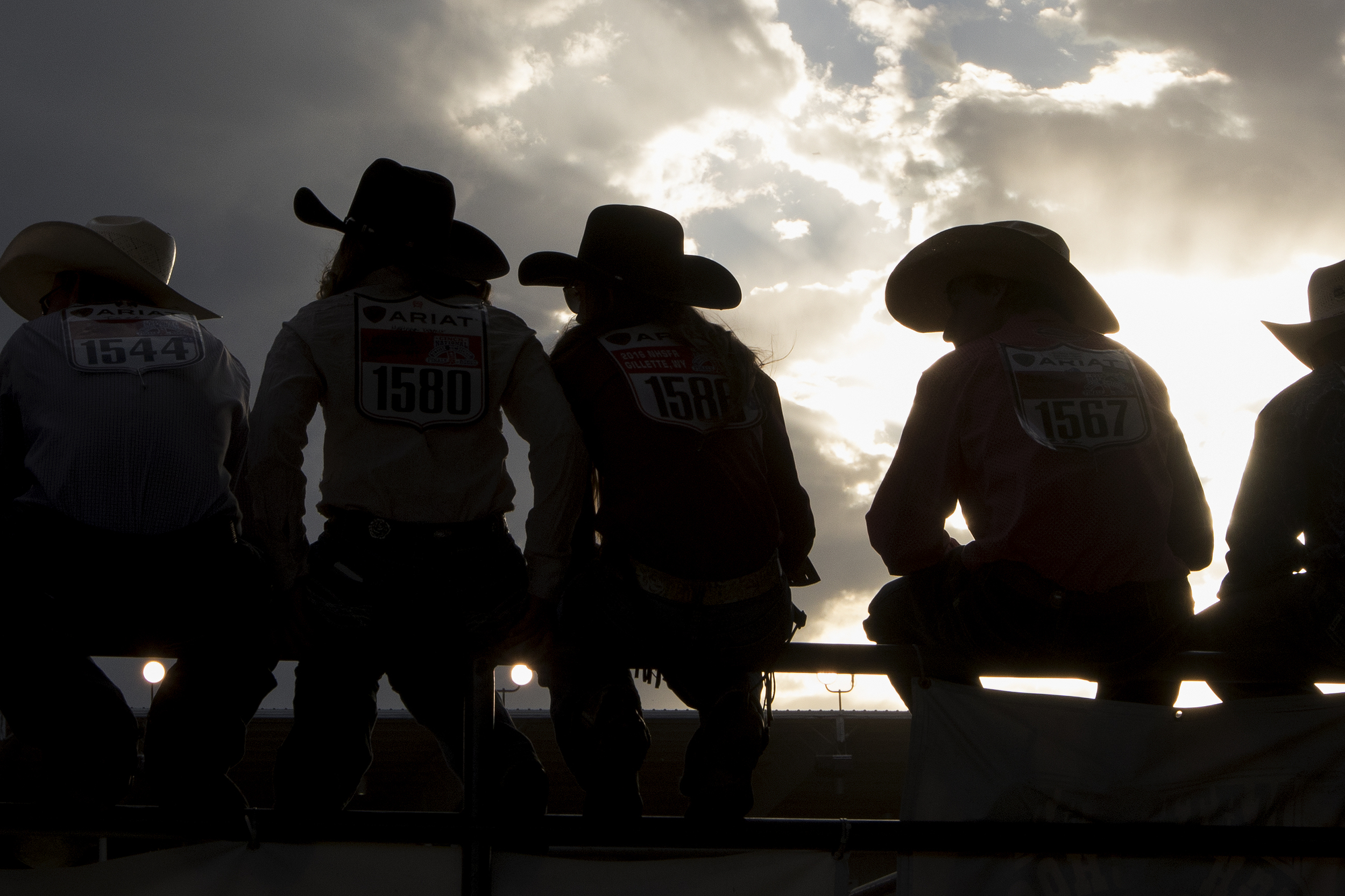 Contestants sit on the railing of the arena during Friday's evening performance of the 2016 National High School Finals Rodeo at Morningside Park.