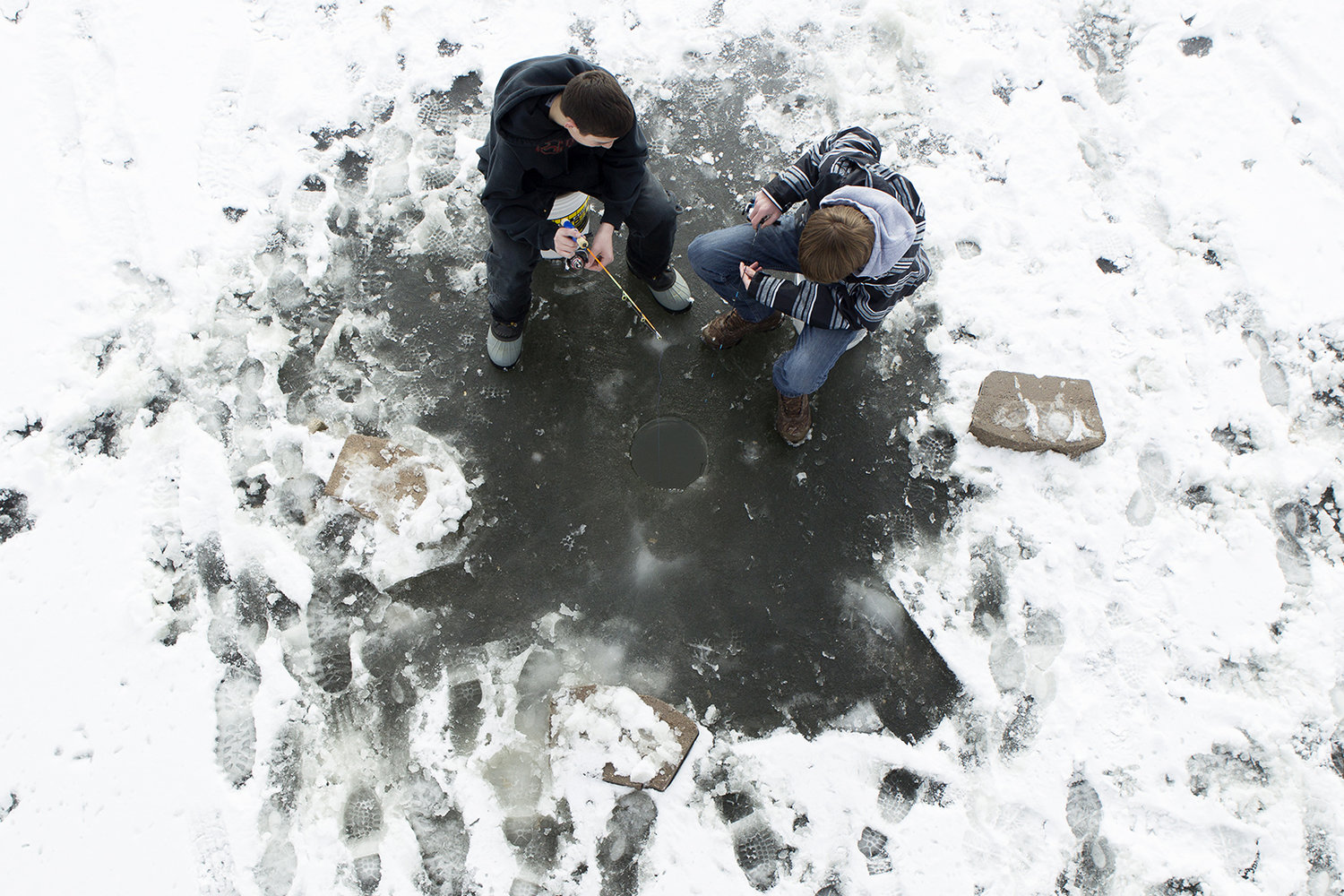 Kain Sherman, left, and Gavin Sidener fish through a hole in the ice on the Gillette Fishing Lake at Dalbey Memorial Park.
