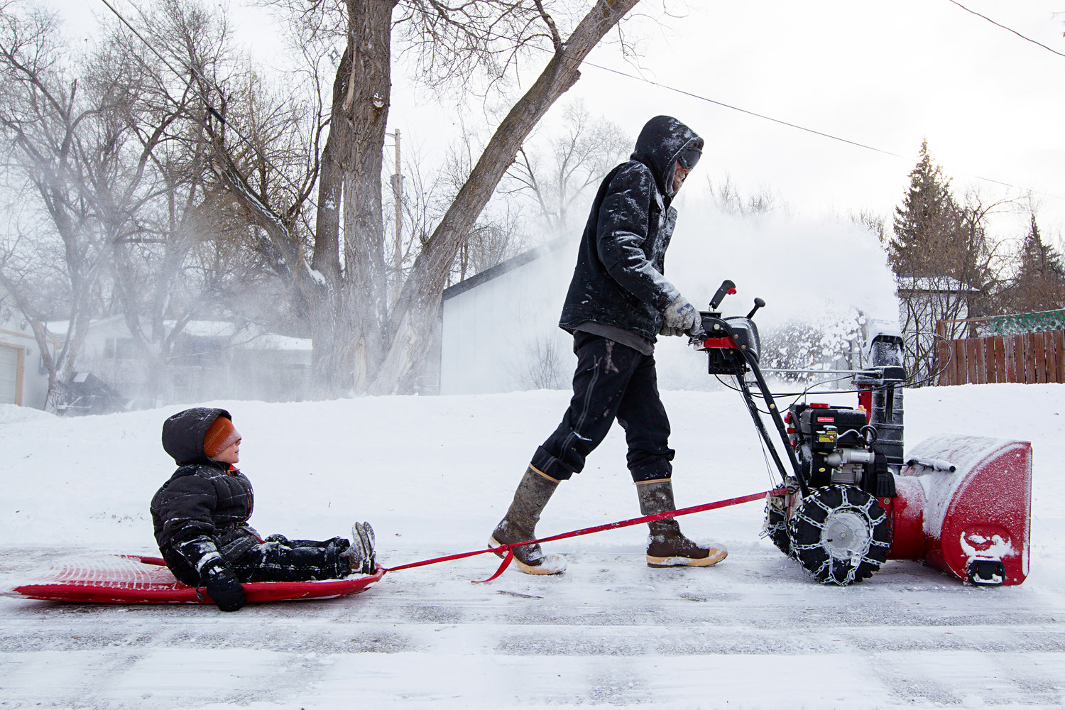 Lucas Strawn pulls his 4-year-old son Logan behind him as he snow blows the parking lot of his mom's office on Monday afternoon. According to the National Weather Service Gillette got 2 inches of snow on Monday, and should expect clear skies and temperatures below freezing for the west of the week, with more snow possible Friday night.