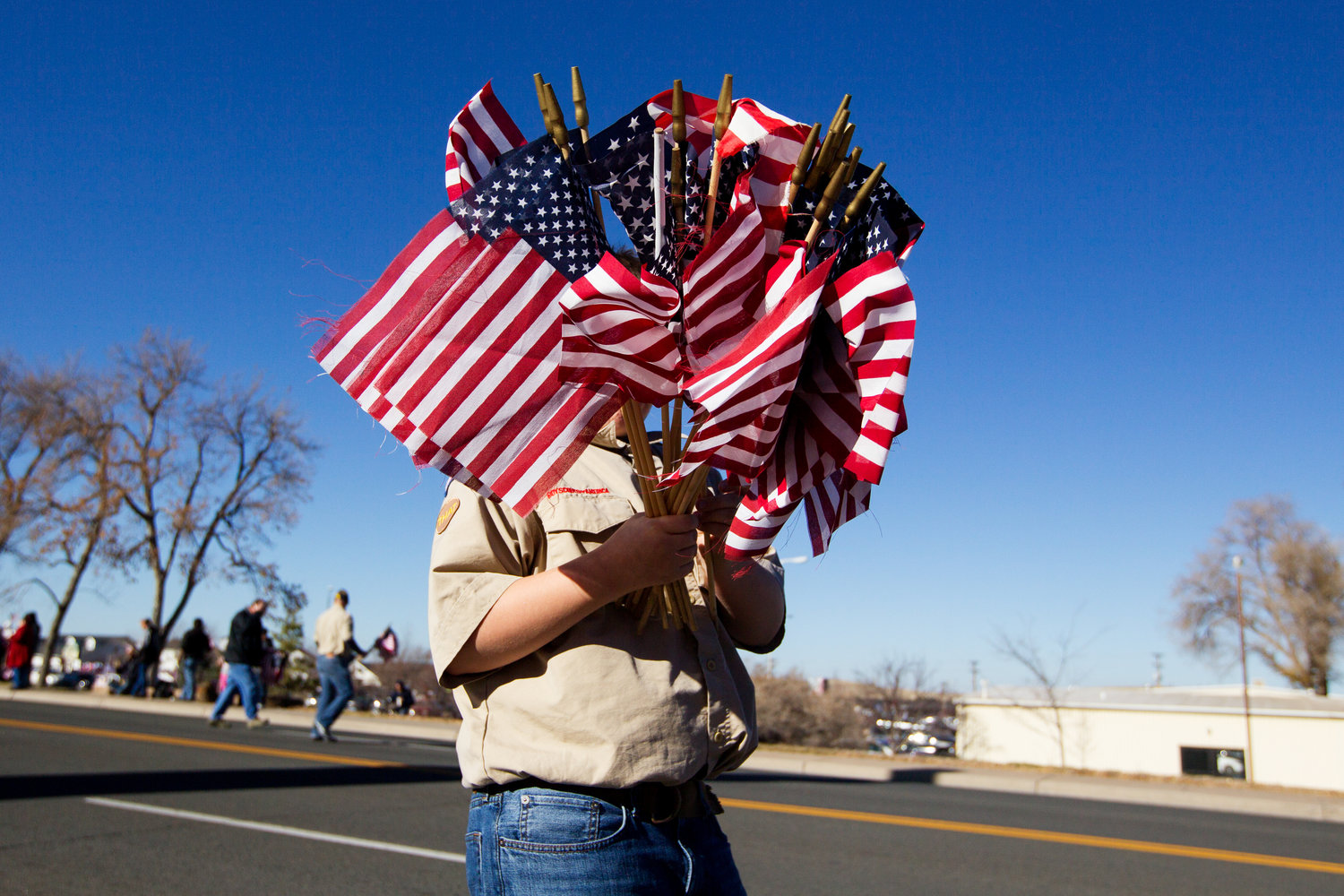 Duncan Davidson, 12, carries a handful of flags while passing them out to bystanders before the Veteran's Day parade on Friday afternoon in downtown Gillette.