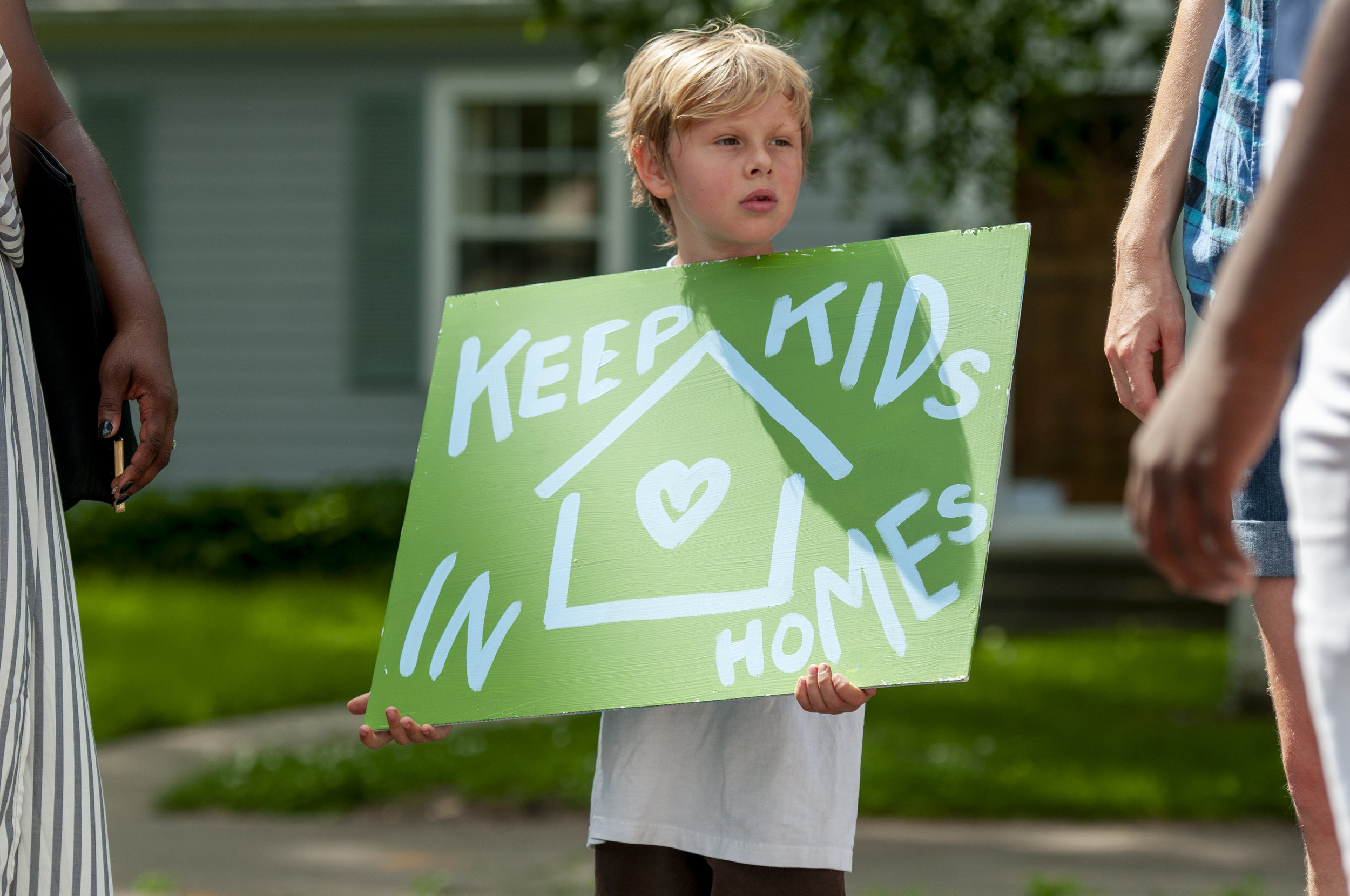 A child holds a sign in support of tenants in South Minneapolis during a prayer vigil on July 14, 2019. The renters are fighting their landlord in court, and on the streets, to block evictions and to convince him to sell them their apartment buildings so the tenants can own and run them as cooperatives.