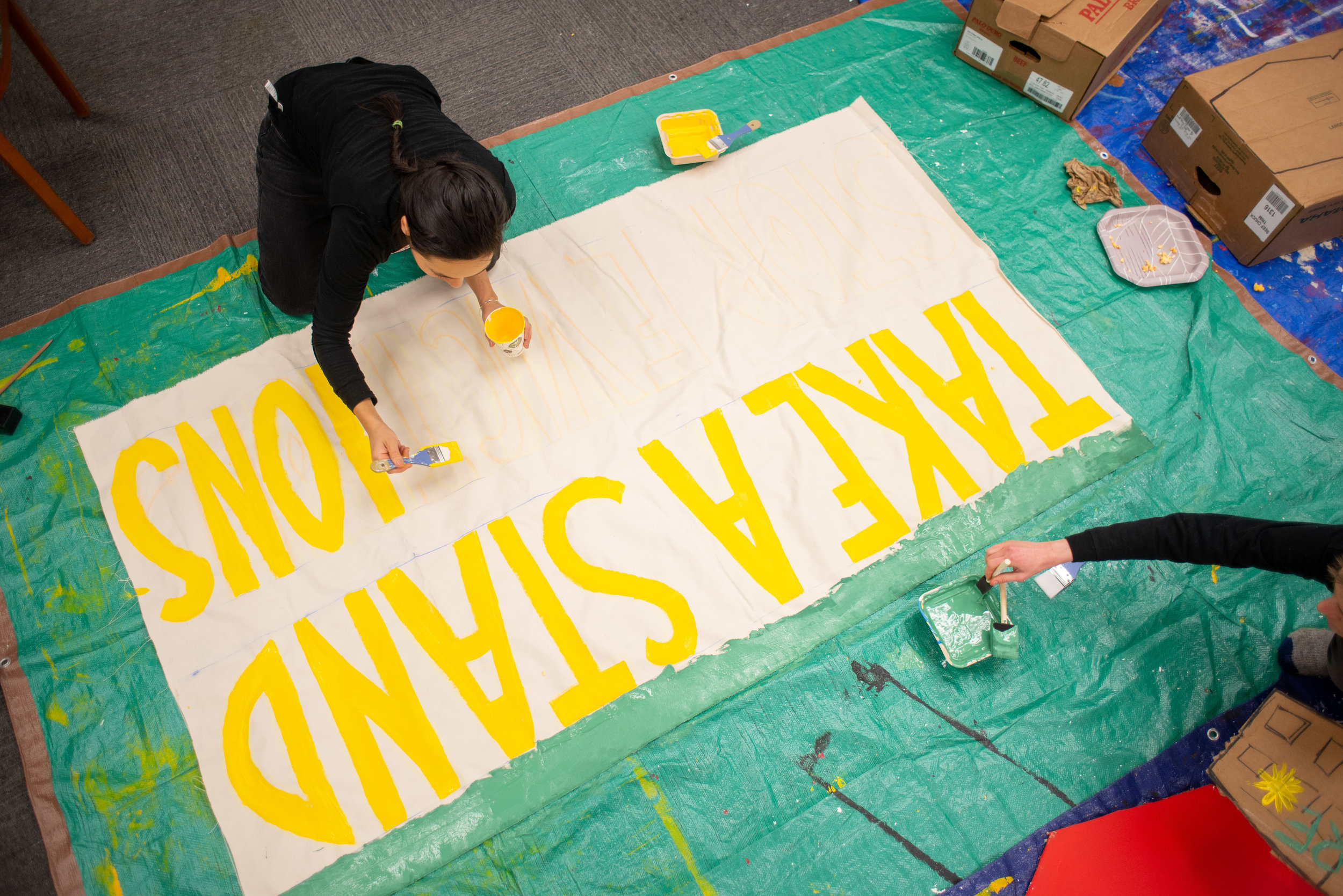Volunteers work on painting a banner in support of residents in South Minneapolis on February 27, 2019. The renters are trying to buy their buildings from their former landlord after he was stripped of his rental licenses by the city of Minneapolis.